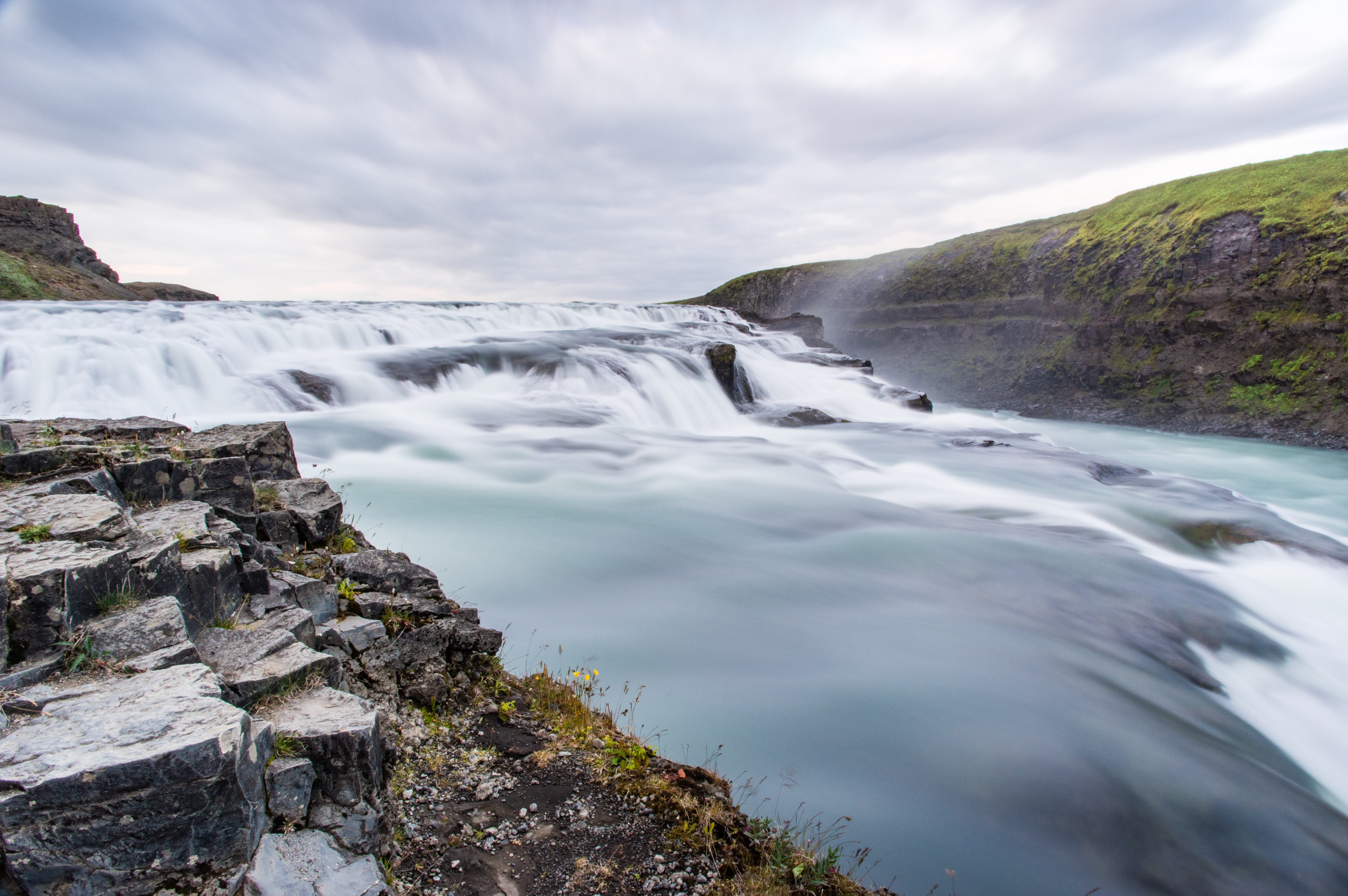 A low waterfall with foamy water flowing down between mossy rocks