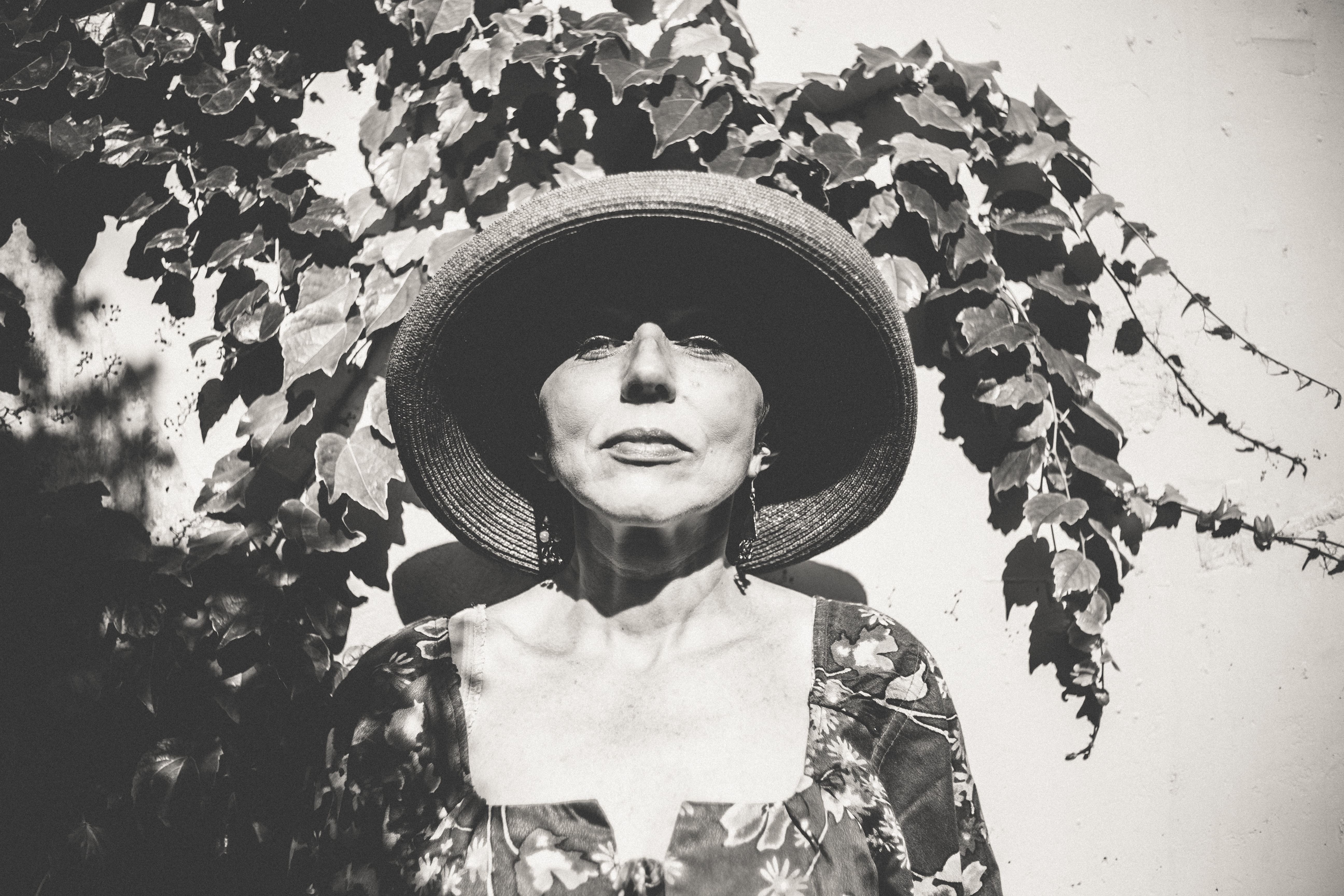 Black and white shot of woman in straw hat in front of wall with ivy vine