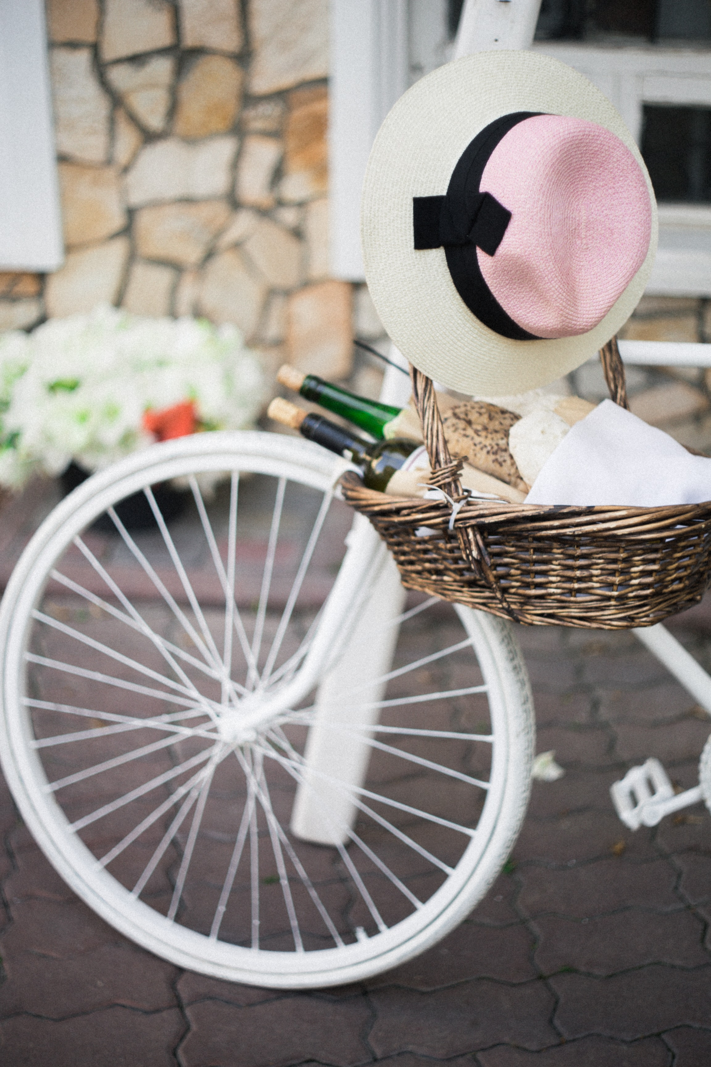 A basket with two bottles of wine and fresh bread hanging from the handlebar of a white bicycle
