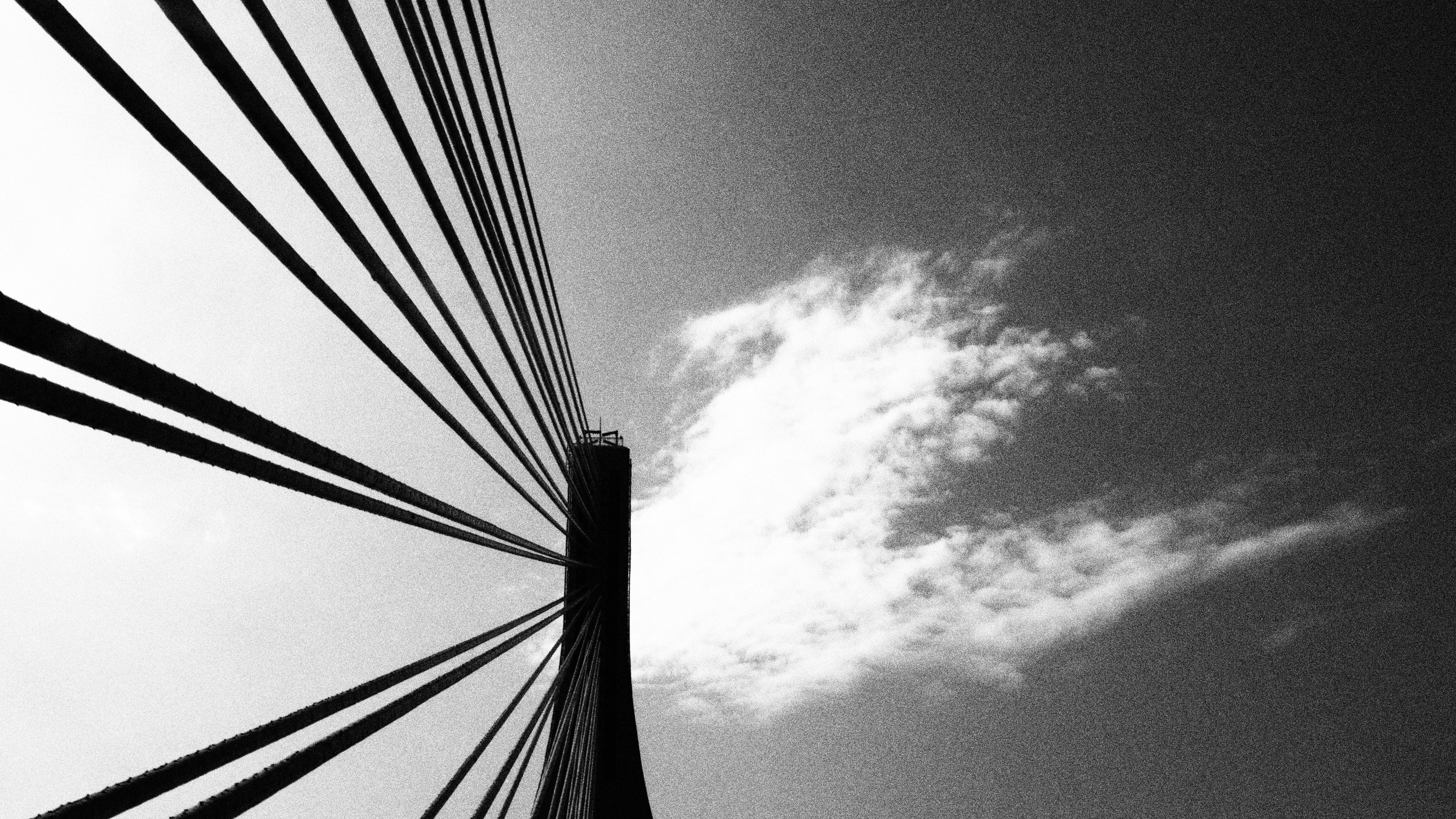 Black and white shot of steel bridge architecture from below with cloudy sky from below