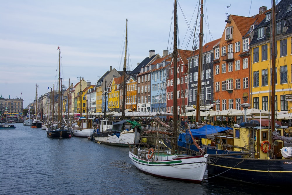assorted-color boats beside assorted-color buildings at daytime