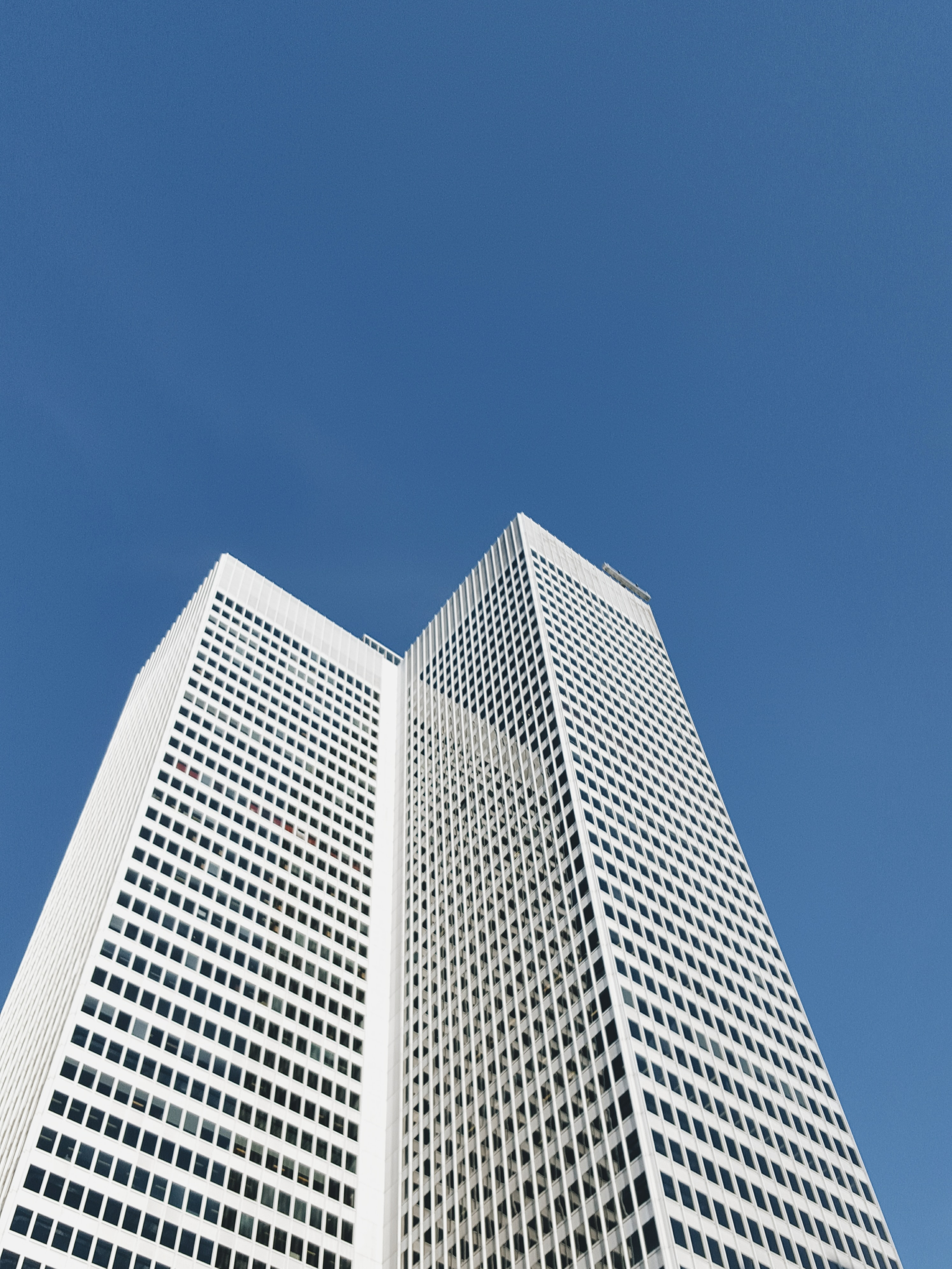A white high-rise in Montreal under a blue sky