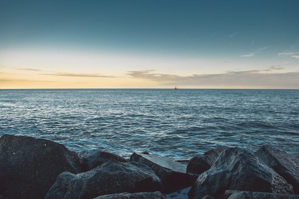 rock formation beside ocean during daytime