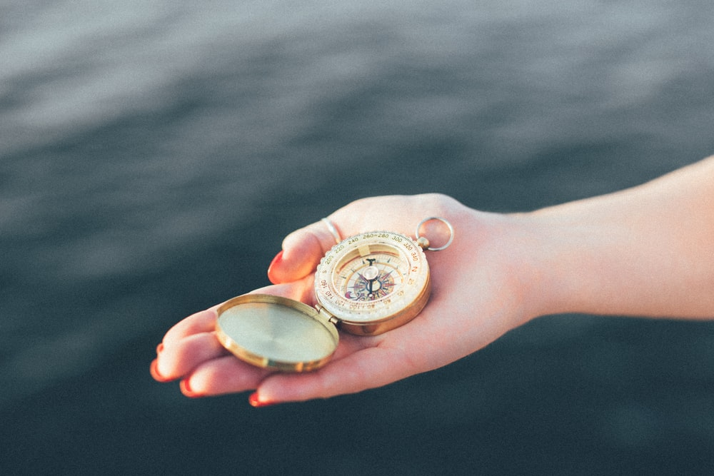 person holding gold-colored pocket watch