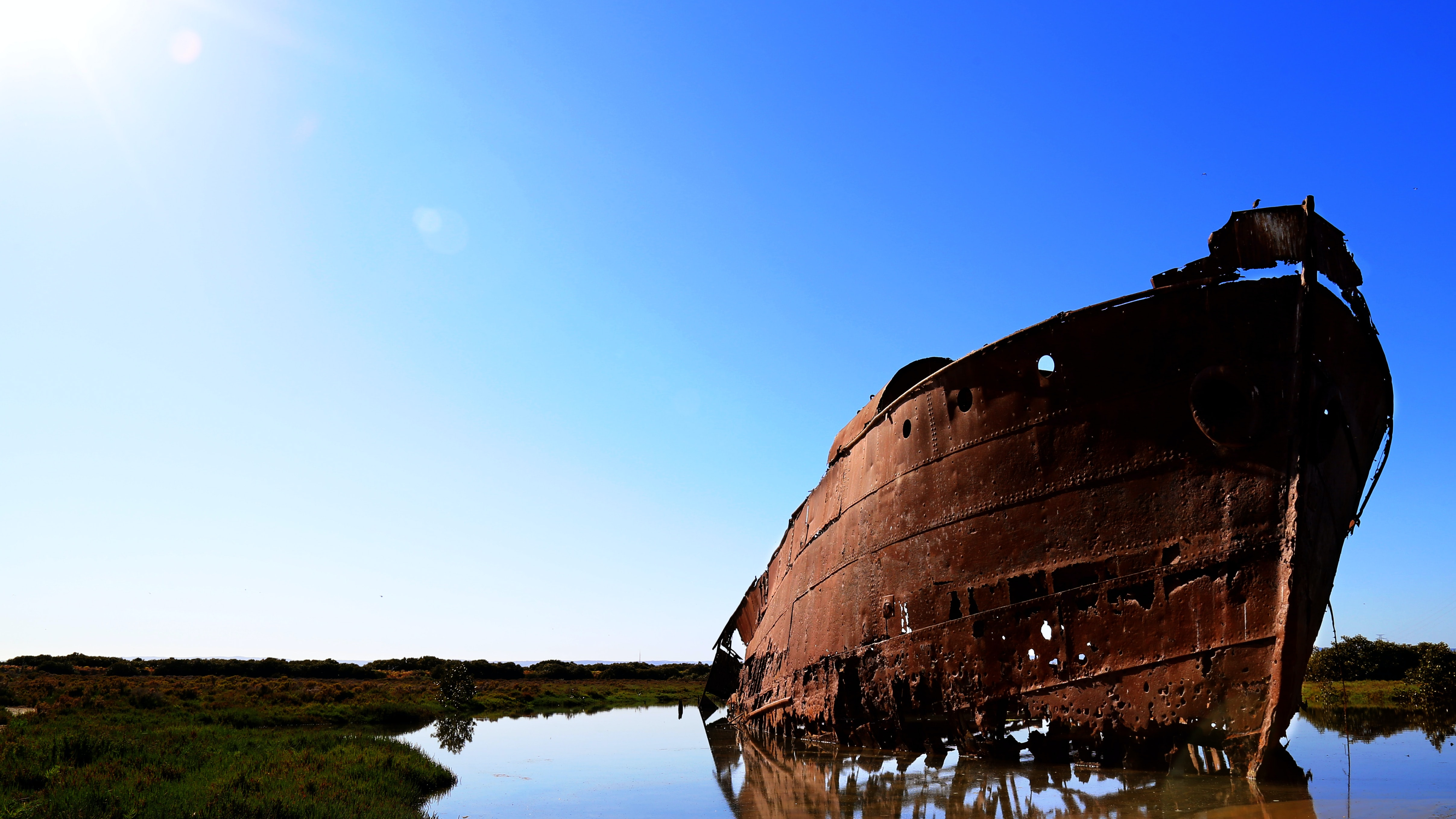 rusted boat near shore under blue sky