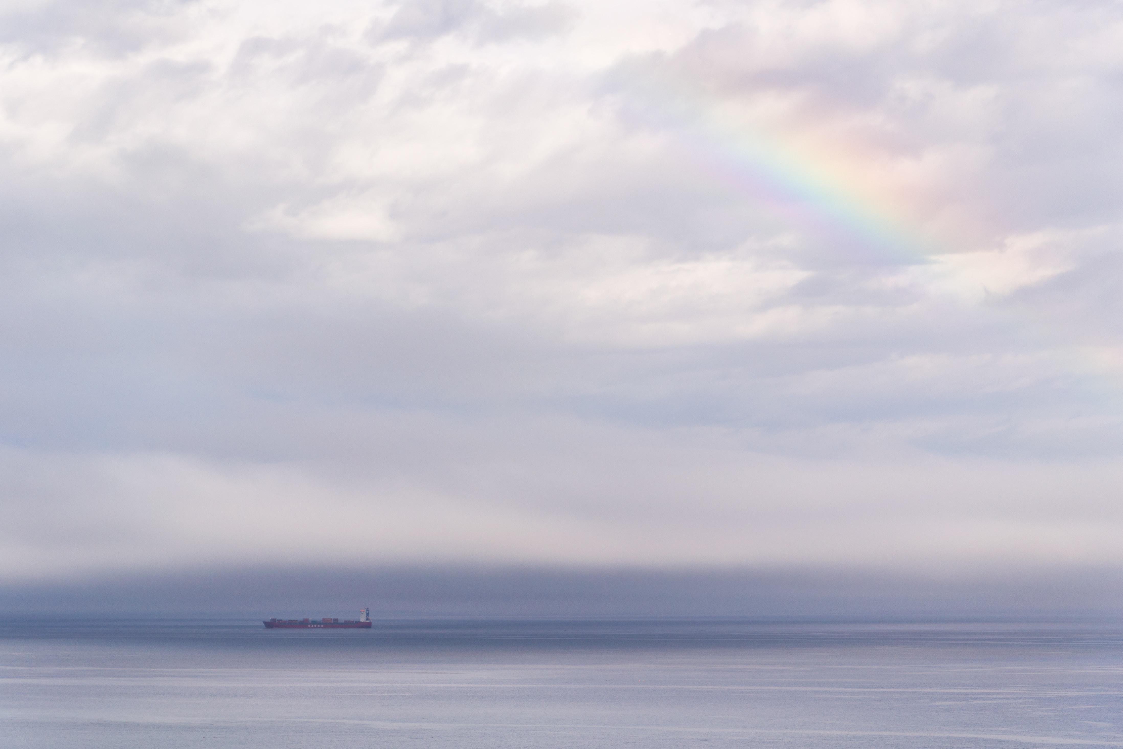 vessel on ocean under cloudy sky with rainbow