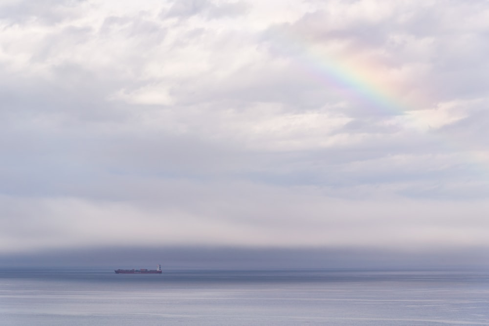 vessel on ocean under cloudy sky with rainbow