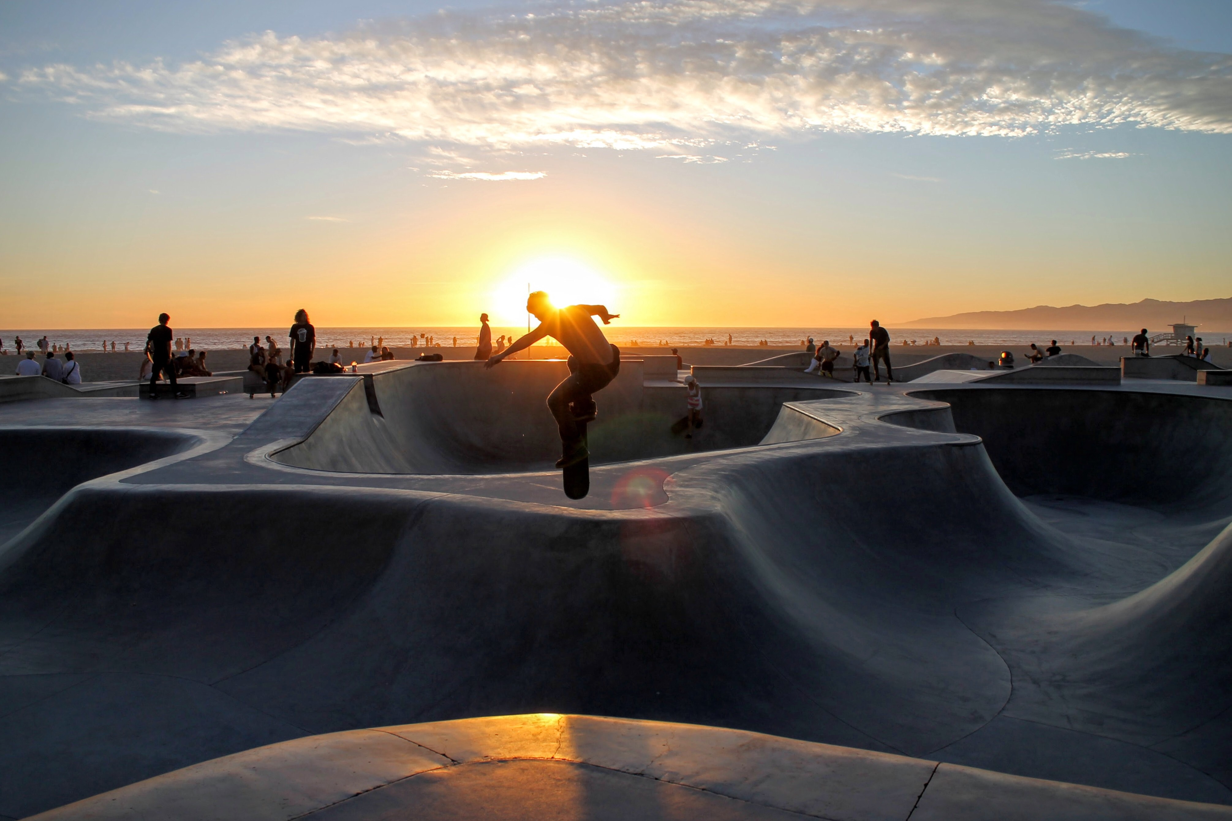A man skateboarding at the skatepark at Venice Beach and Boardwalk during sunset