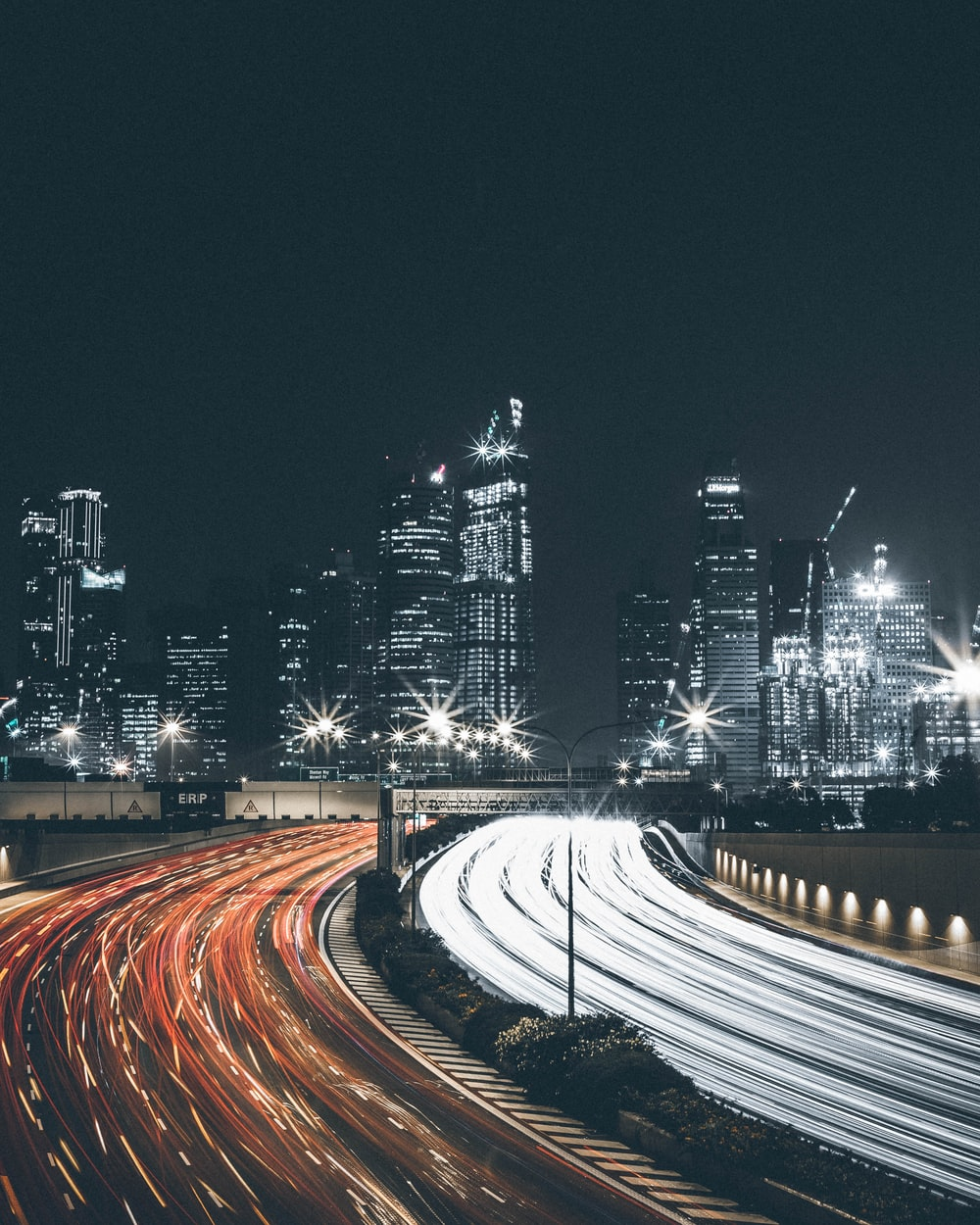 A Photo Of Lit Up City Skyline With Light Trails From Traffic Time