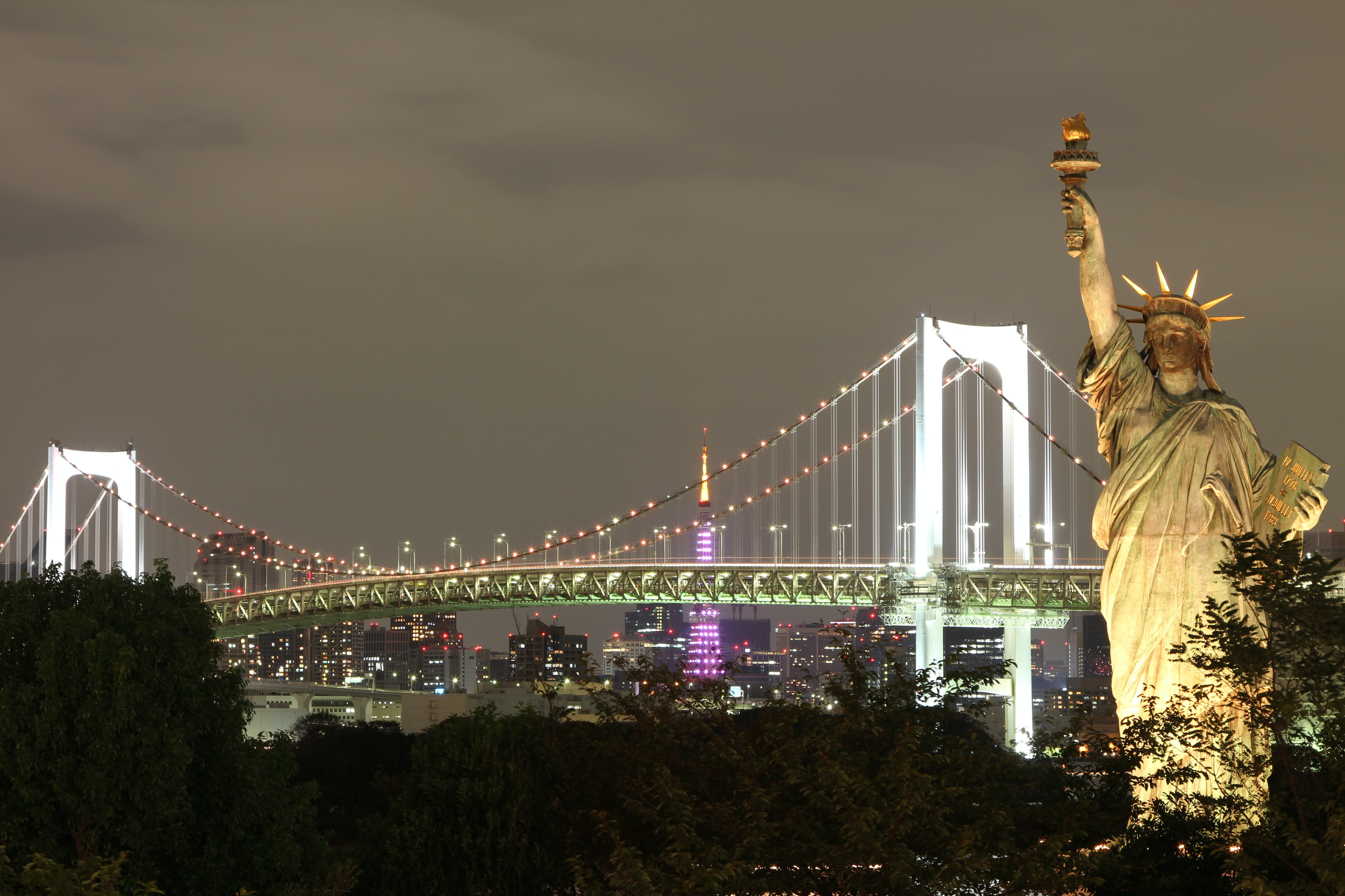 The Statue of Liberty stands in front of a lit up bridge at night in New York City