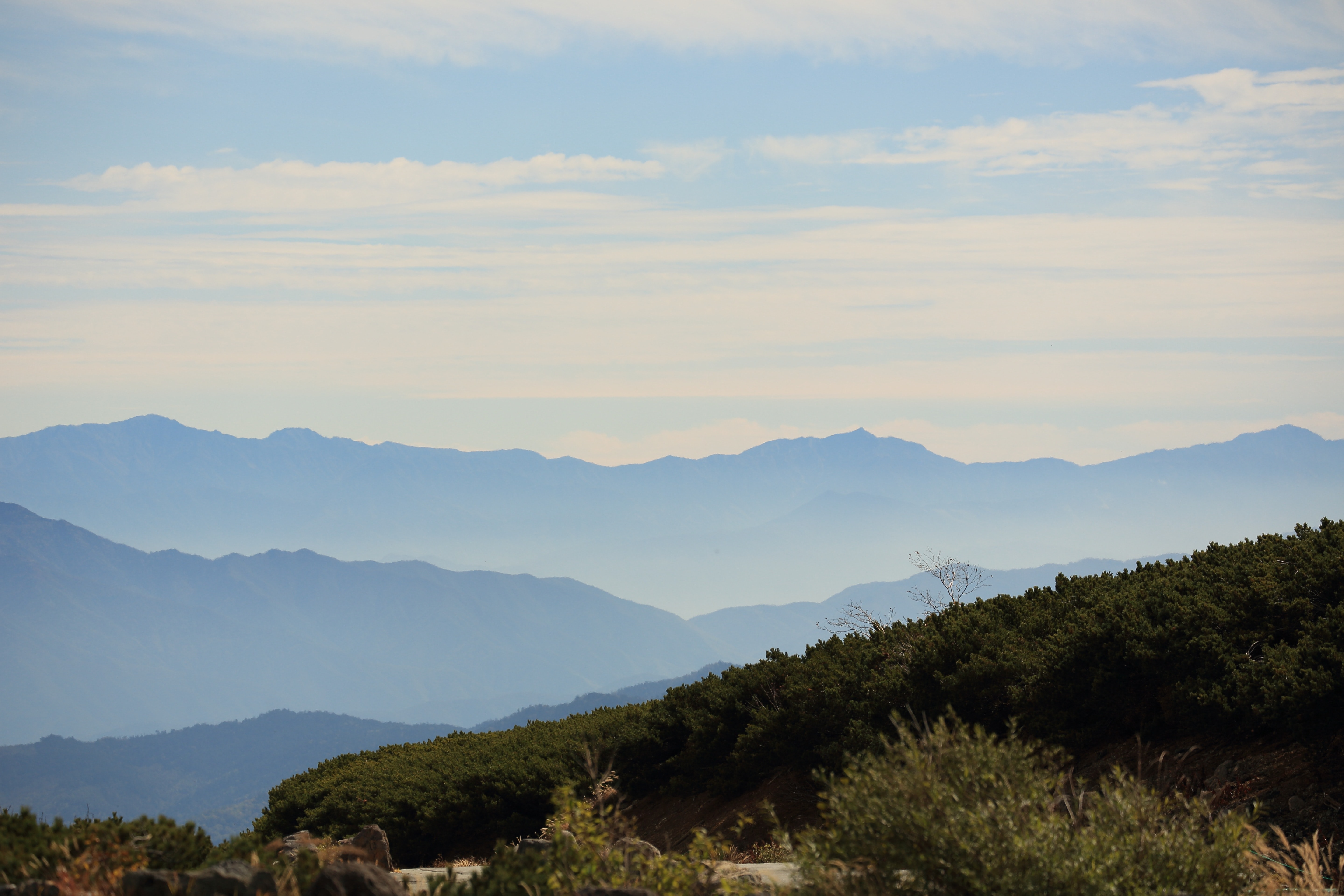 A view on the long silhouette of a long mountain range against a blue sky