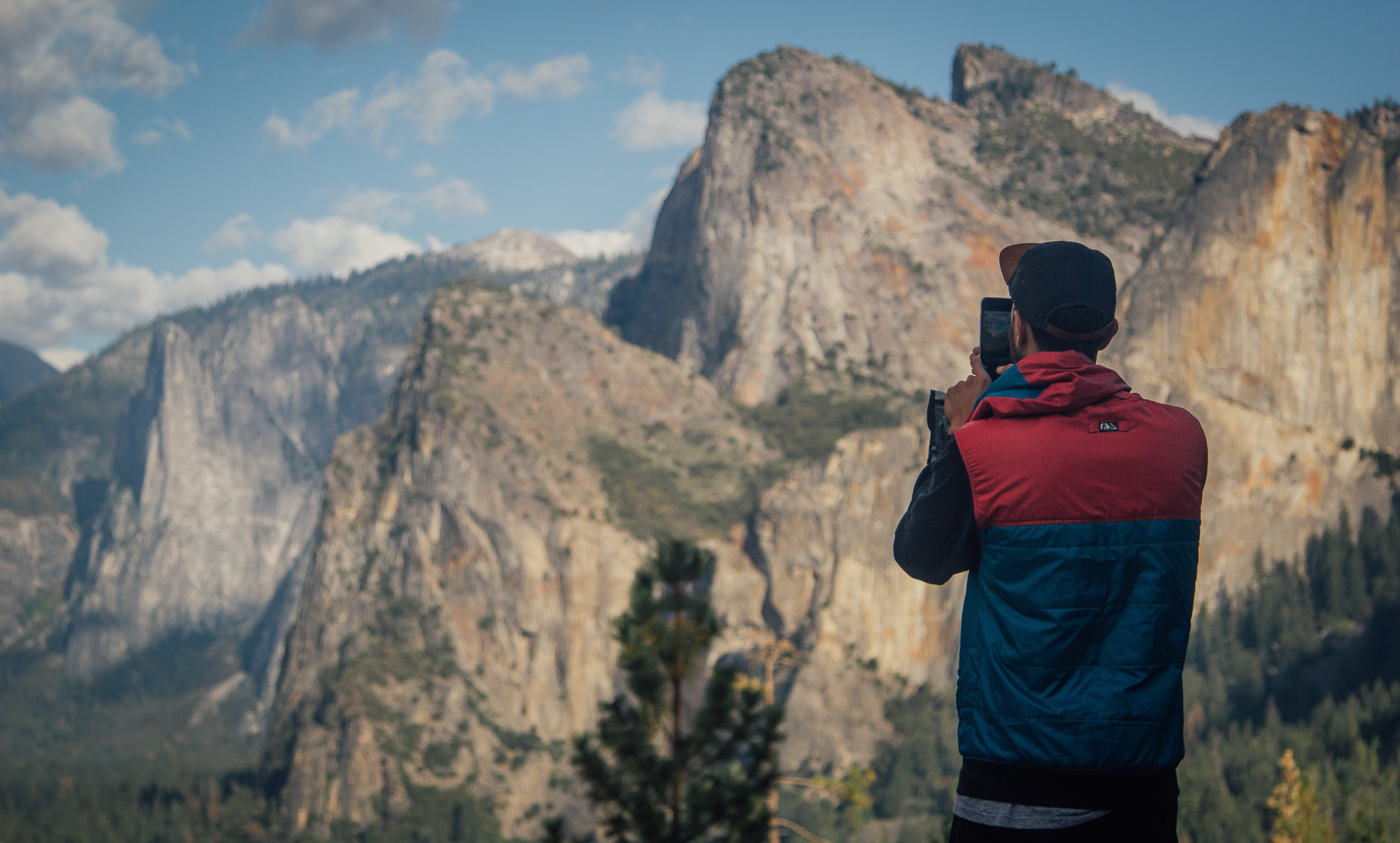 A man taking a photo with his phone in Yosemite National Park
