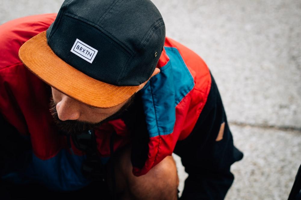 man wearing black and orange Baxin cap looking down