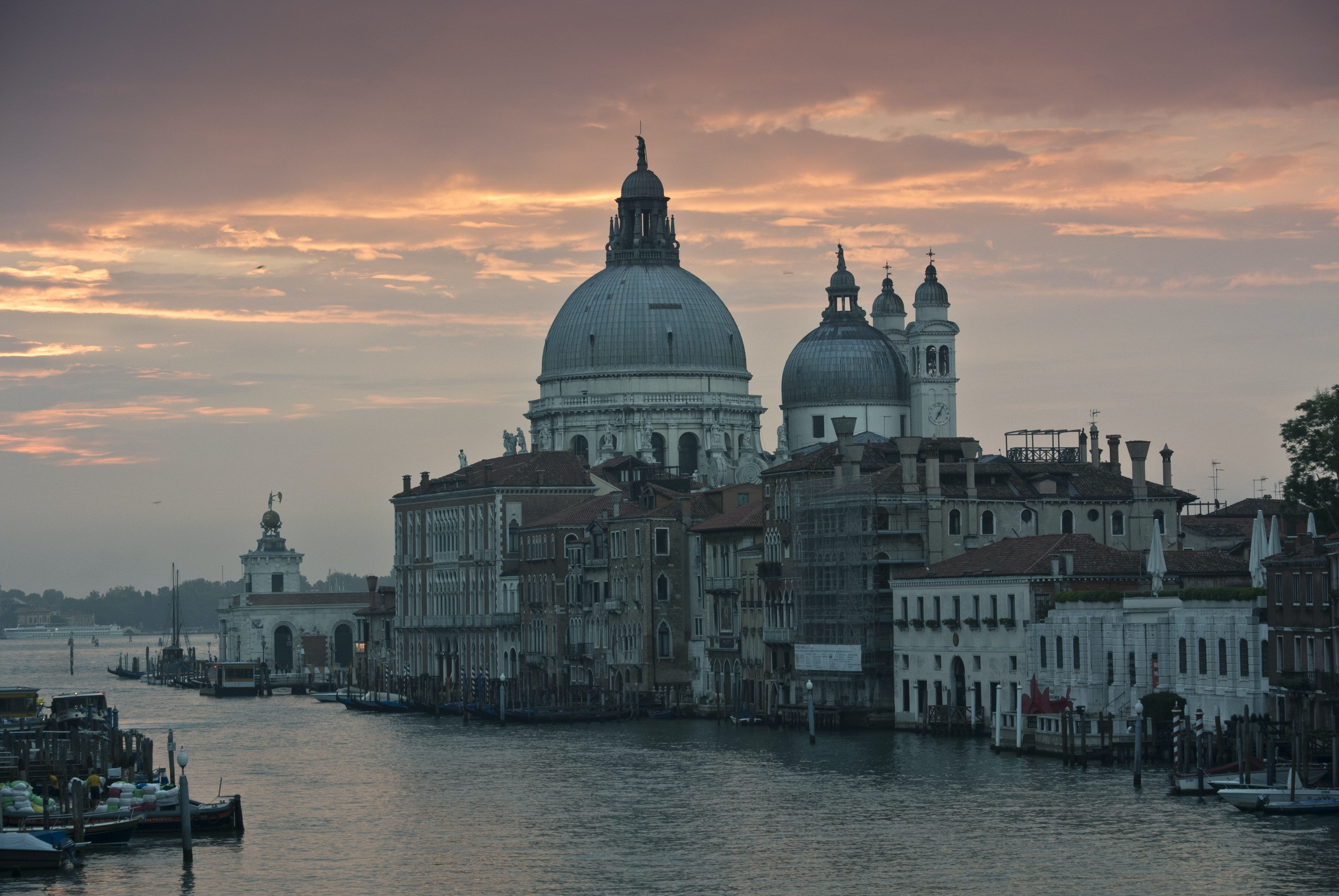Light orange and pink sunset reflected in the water in Venice, with clear cityscape and architecture in detail.