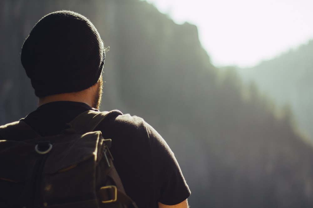 man wearing black t-shirt and knit cap fronting mountains