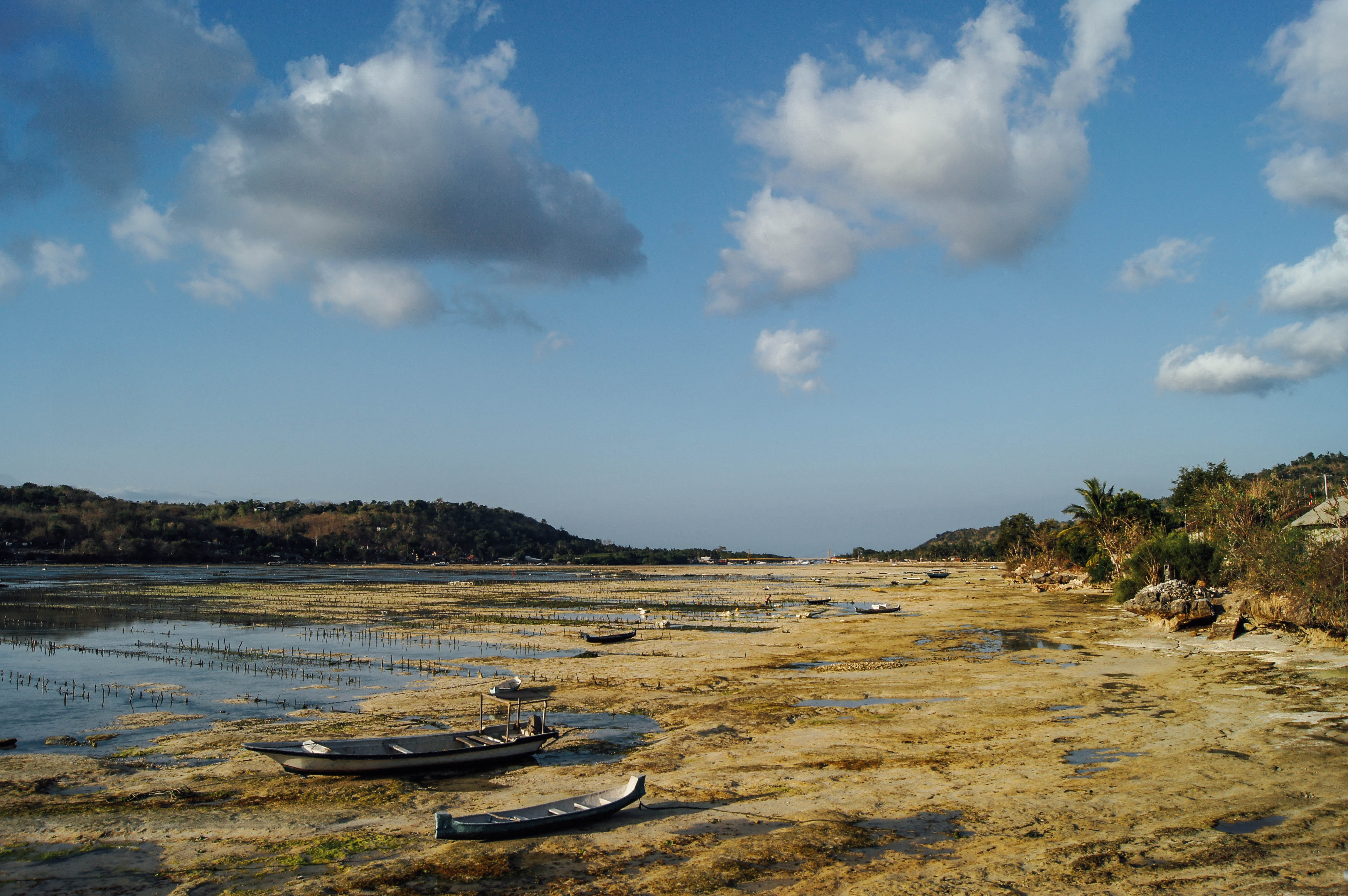 A dry river bed with fishing boats aground