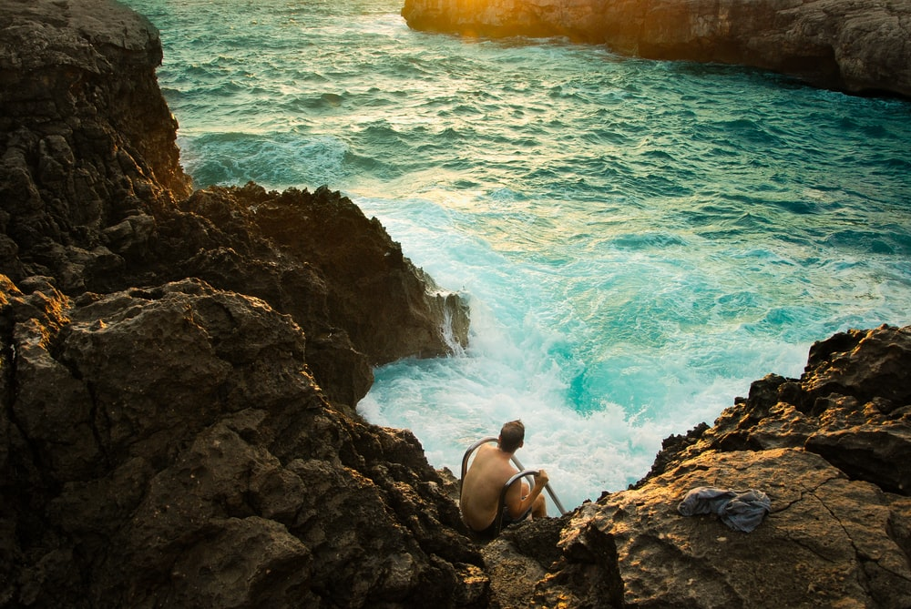 man sitting on rock formation beside body of water