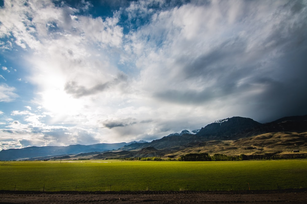 grass field under cloudy sky during daytime