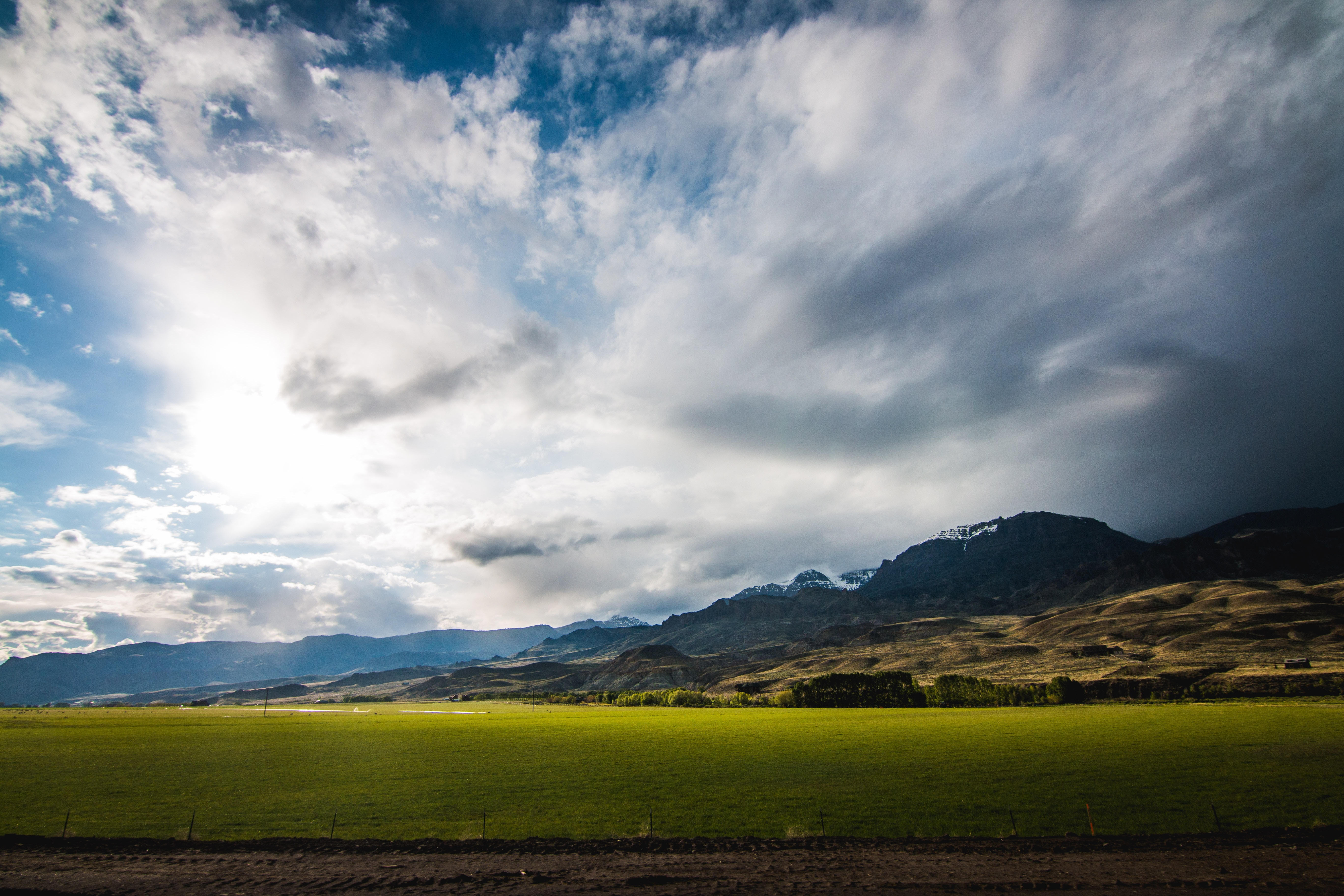 Tranquil pastures in a rural valley below snowy mountains on the horizon