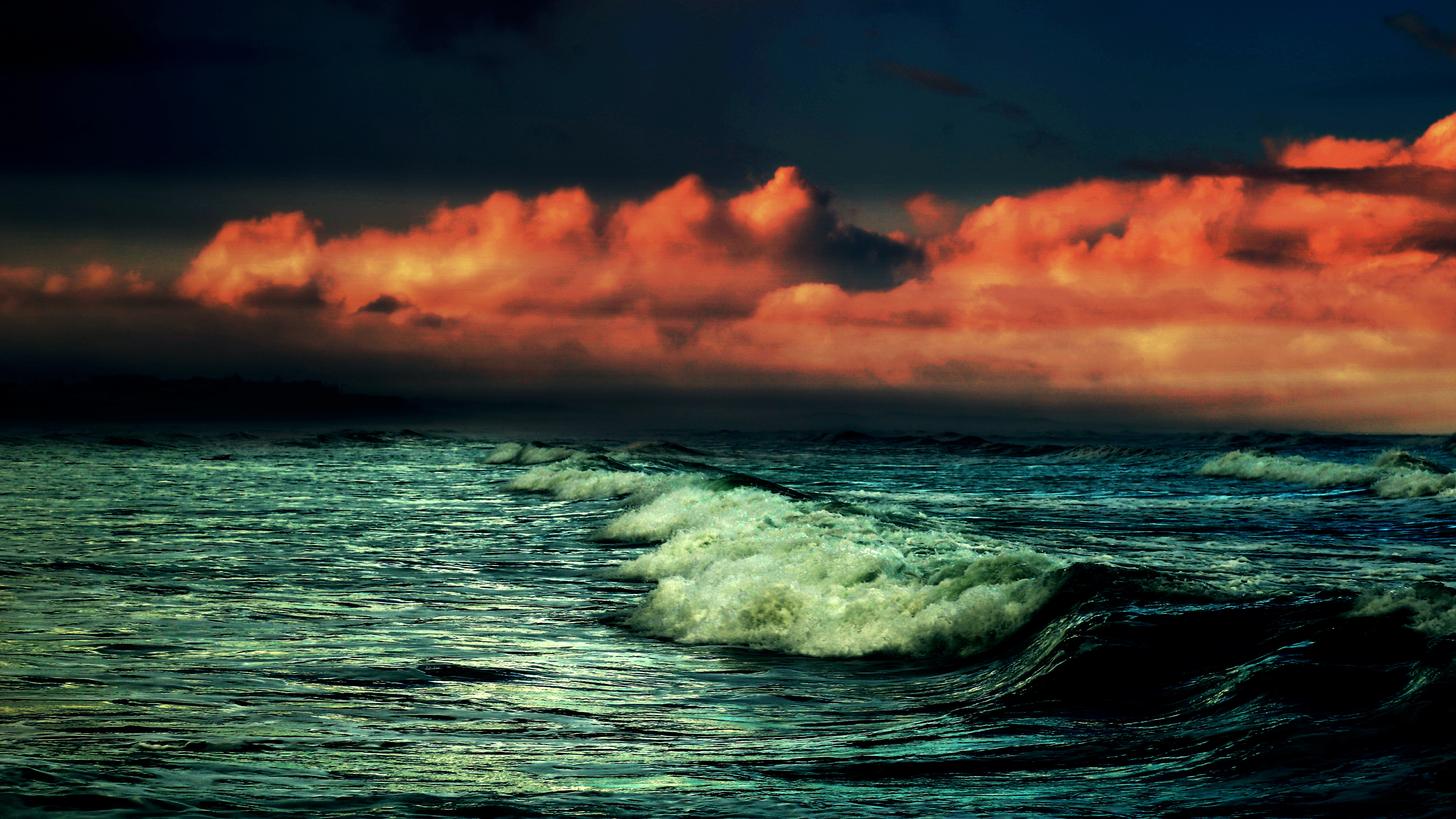 A dramatic shot of dark crashing waves under a red cloudy sky