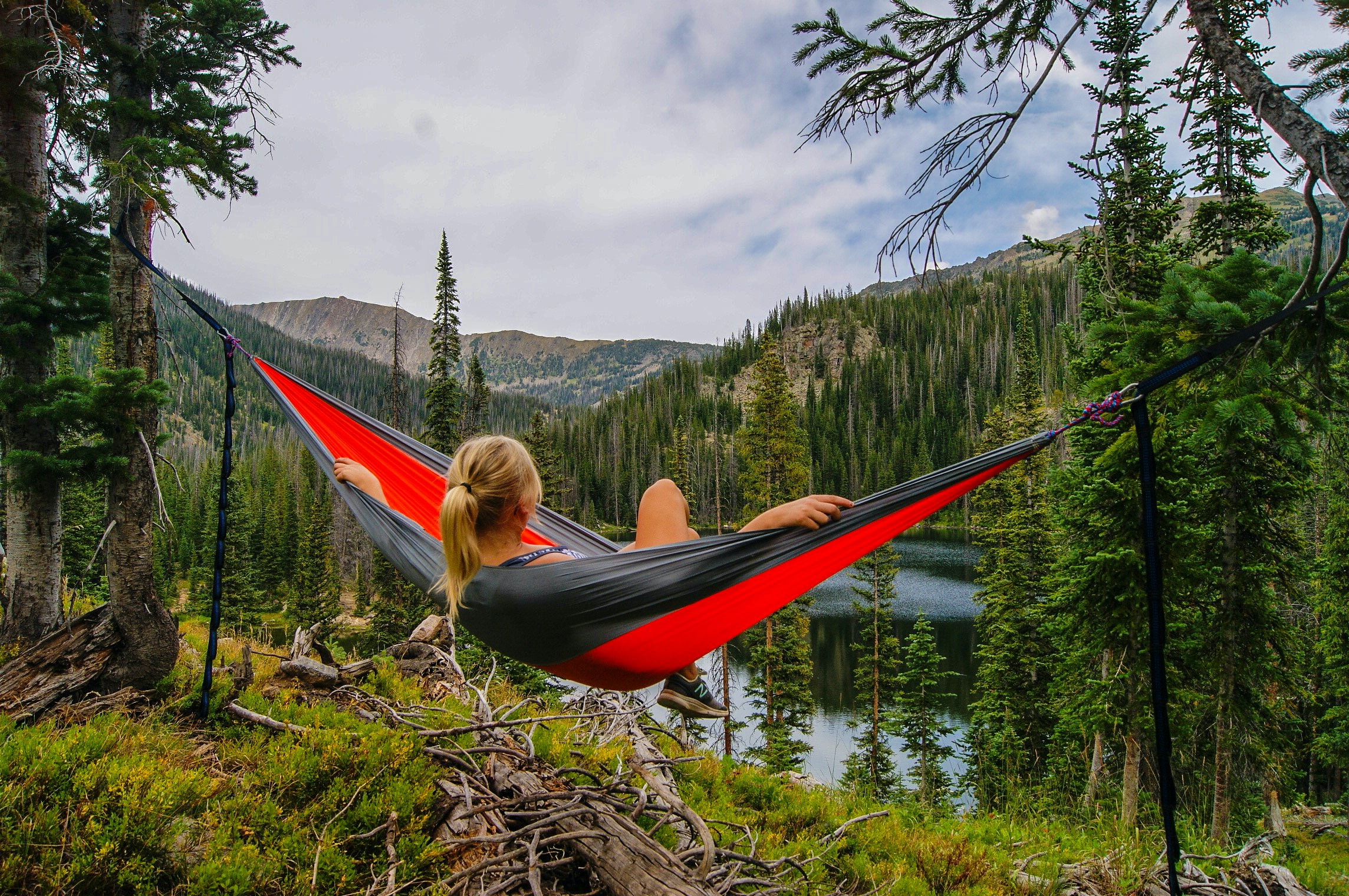 A girl with blonde hair sits in a red and gray hammock overlooking mountains, trees, and water.