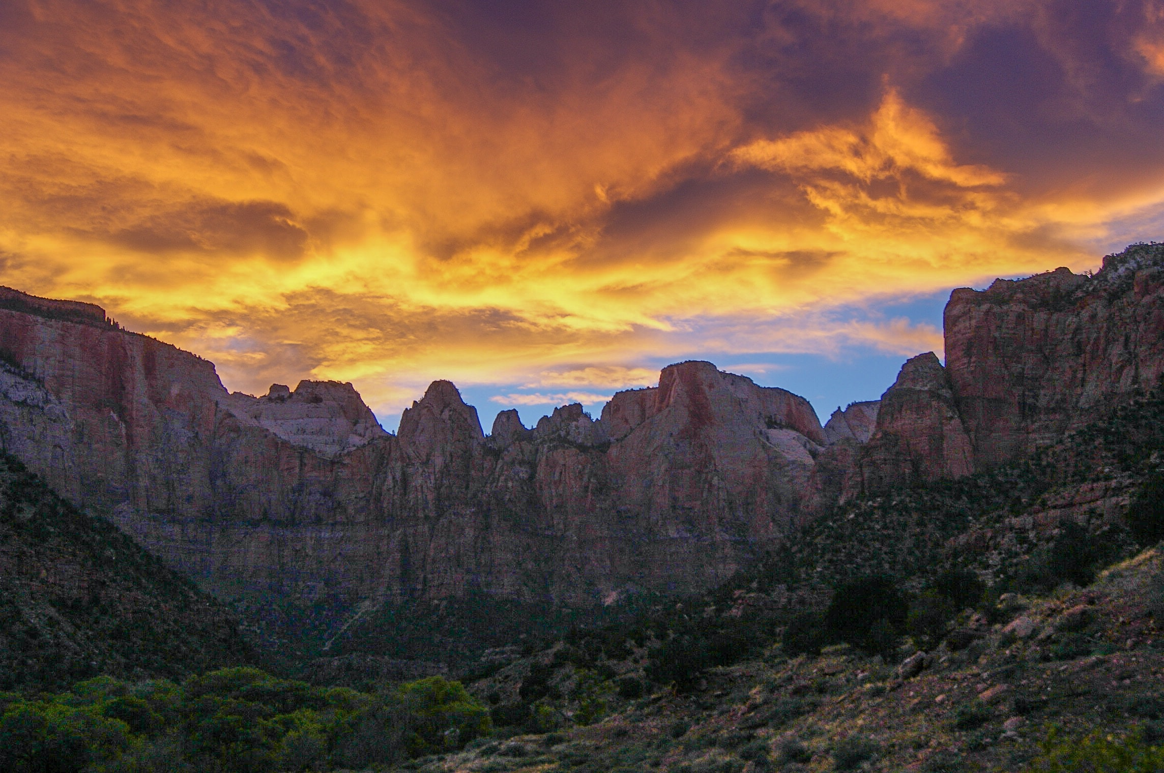 Orange clouds over a rocky mountain landscape in Zion National Park