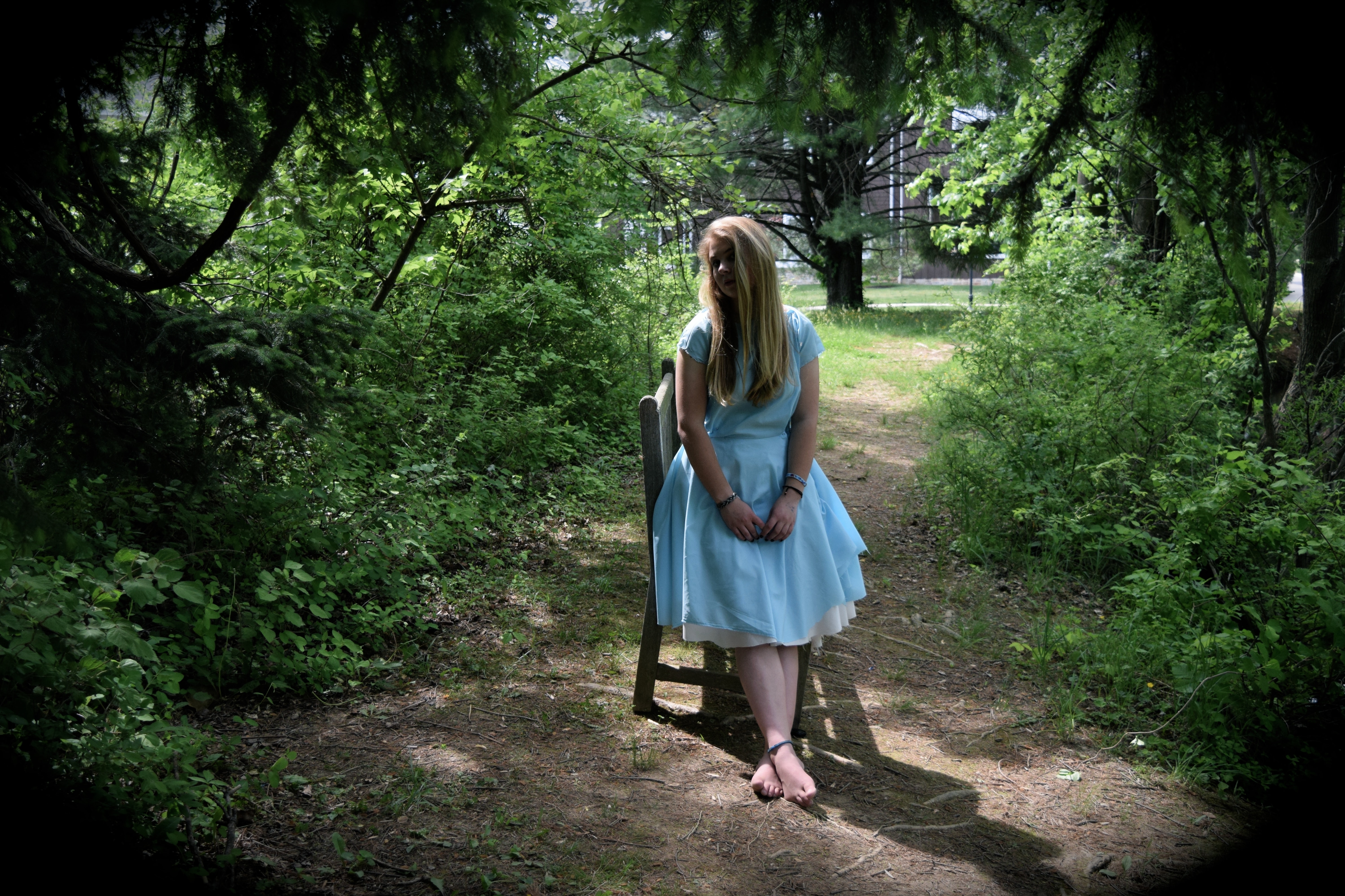 A young adult female in a white dress leaning on a chair in the middle of the woods.