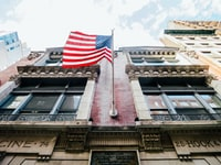 low angle photography of waving U.S.A. flag hang on bricks wall