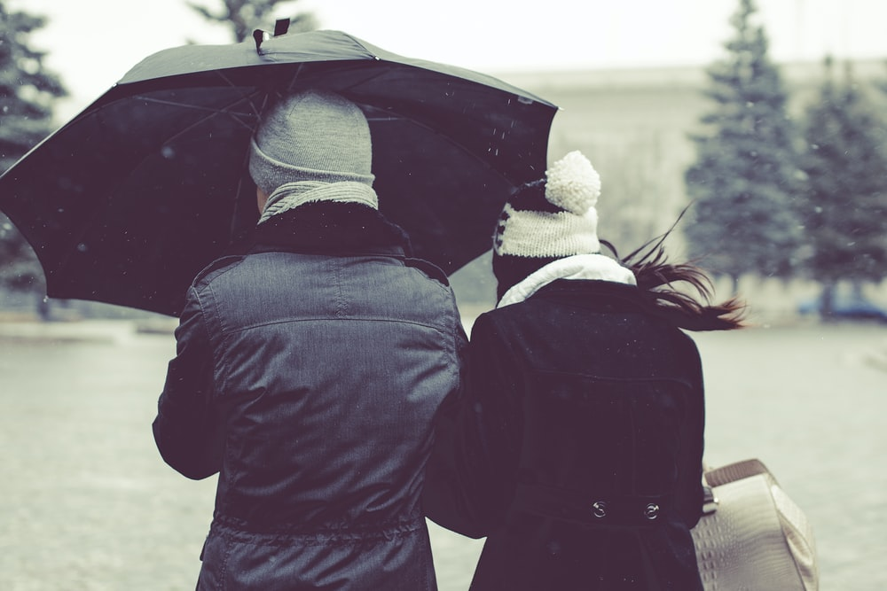 back view photography of two person under umbrella on snowy day