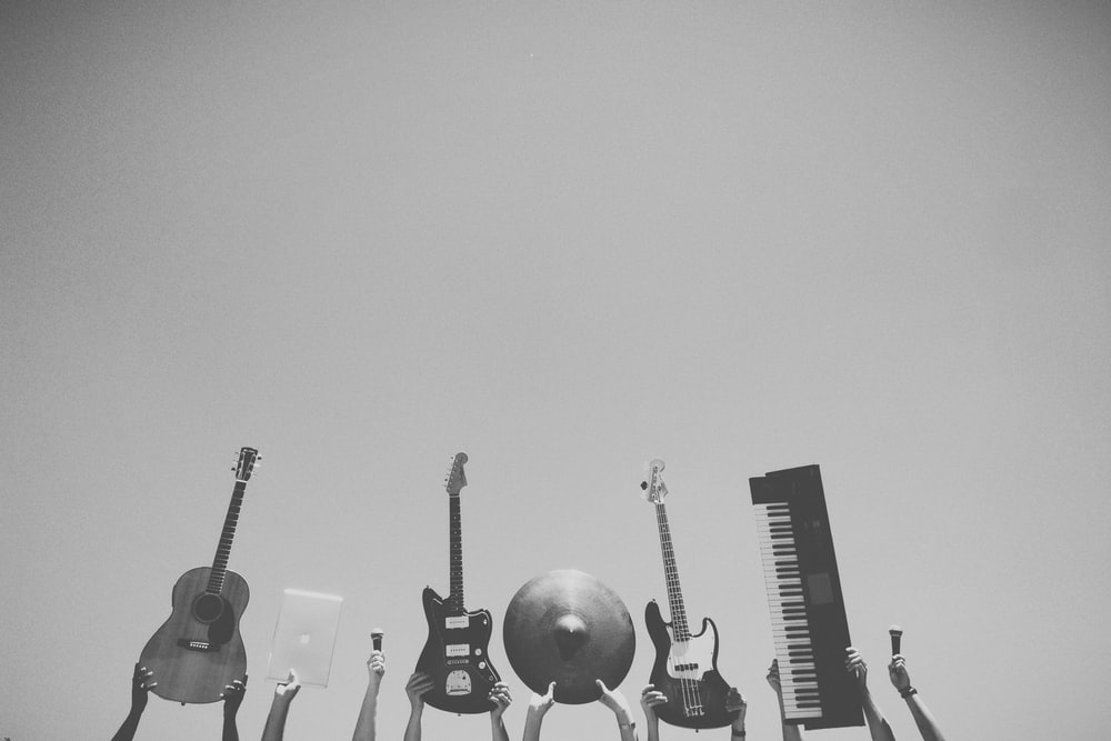 grayscale photo of people holding assorted music instruments