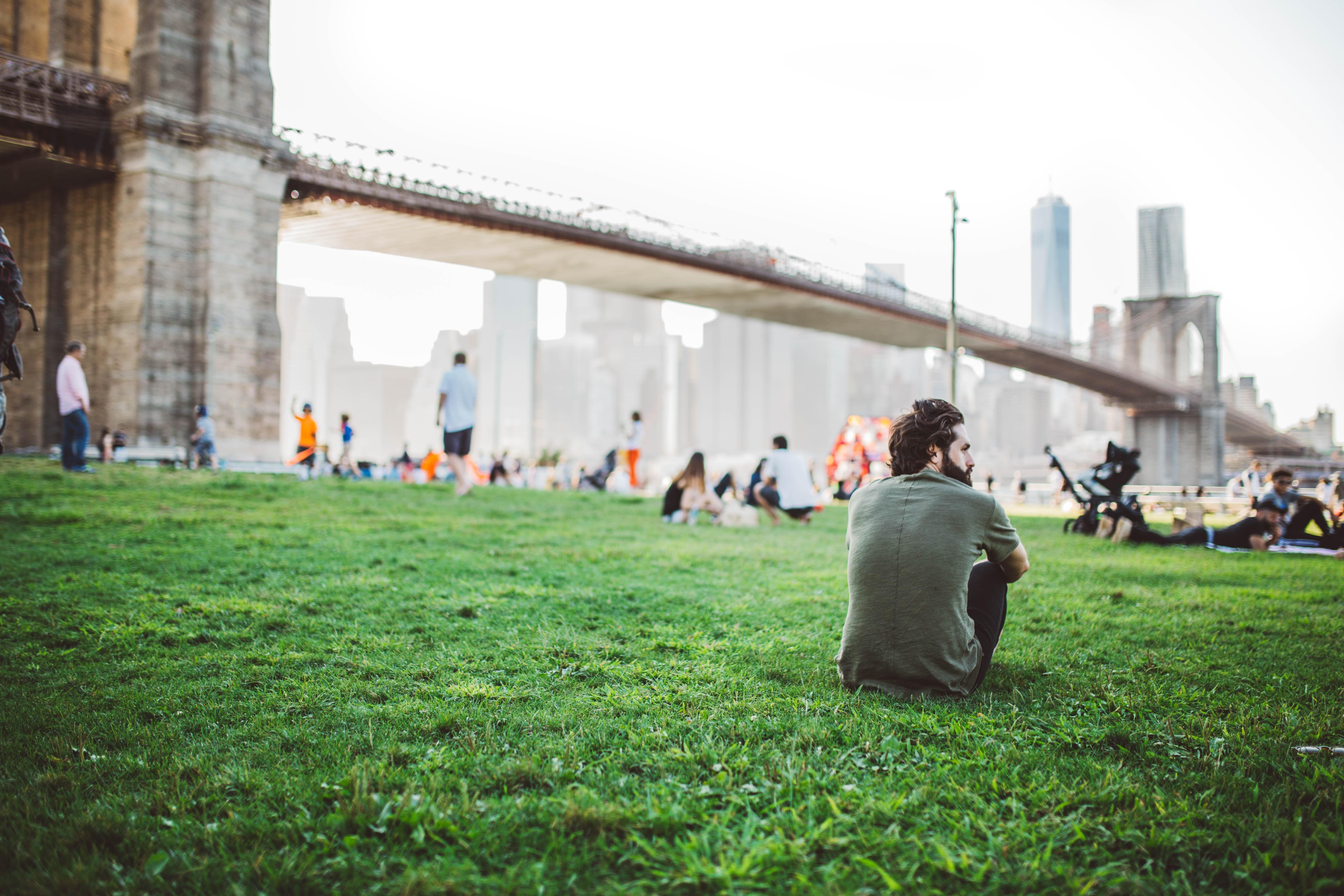 People relaxing on a lawn near the Brooklyn Bridge