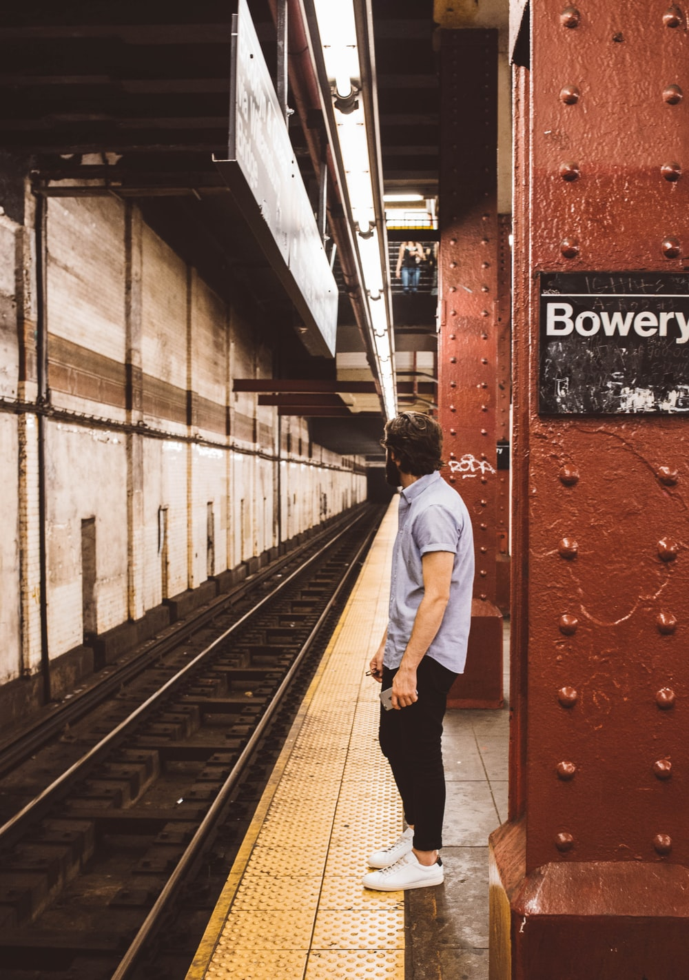 man standing beside subway platform