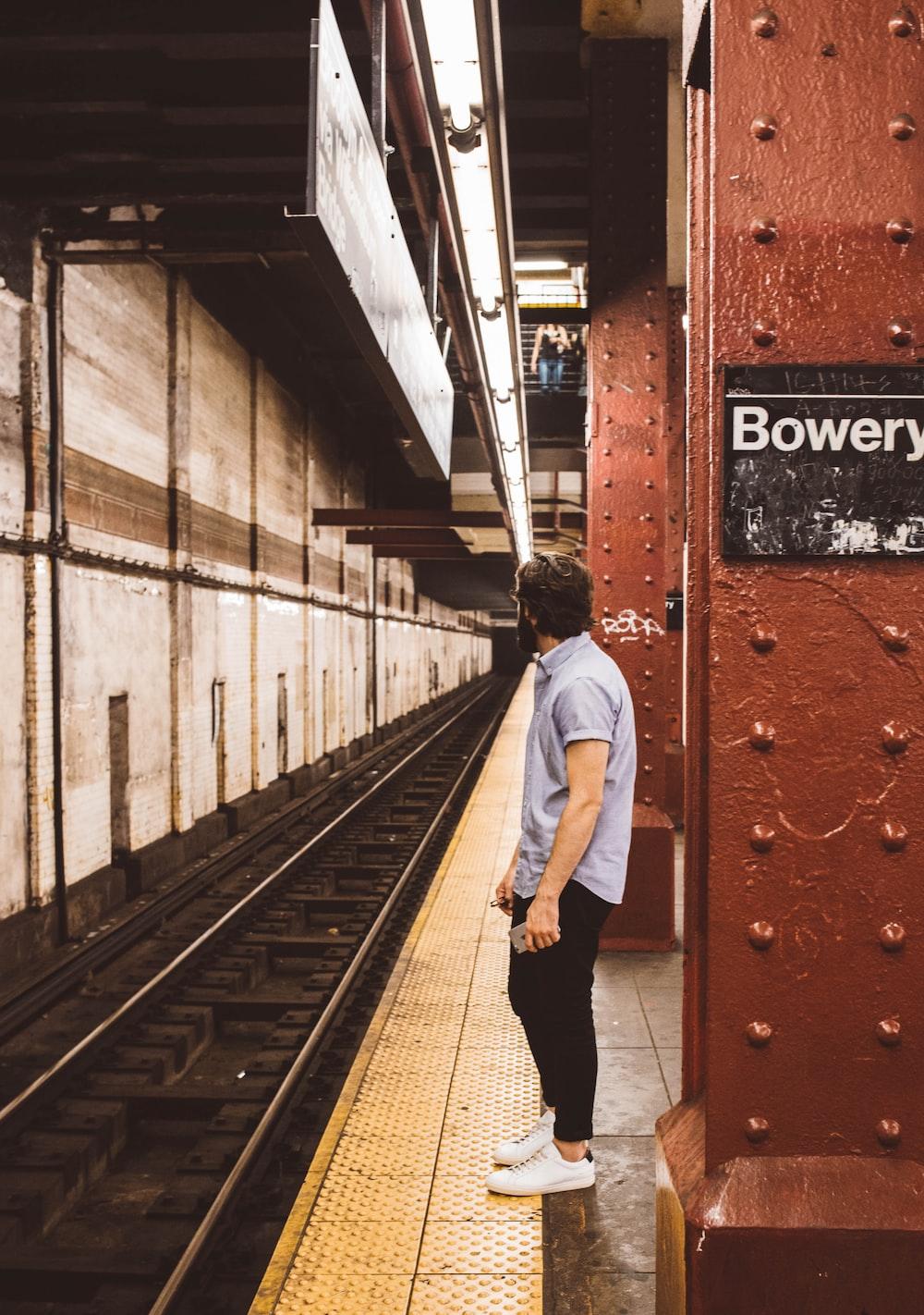 man standing beside subway platform