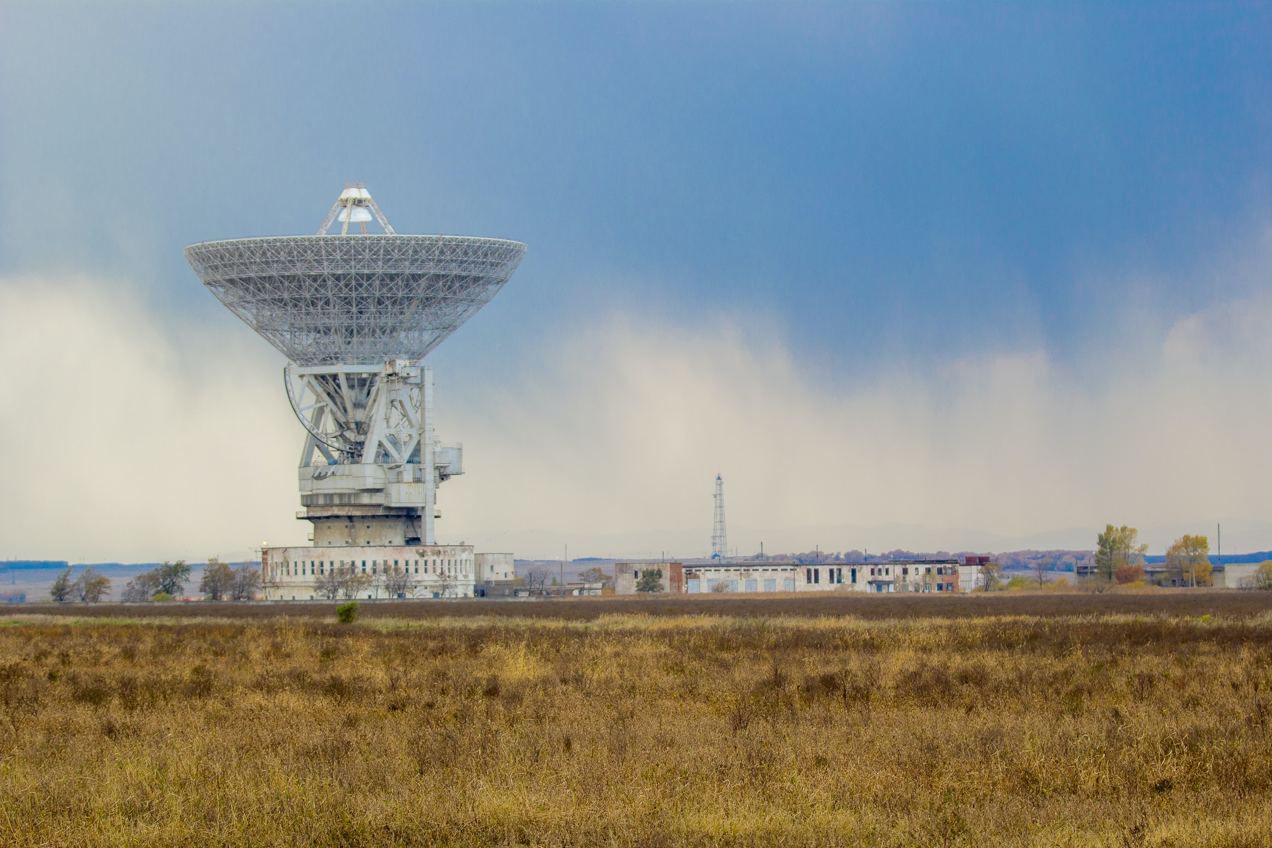 Satellite among technological buildings in a field