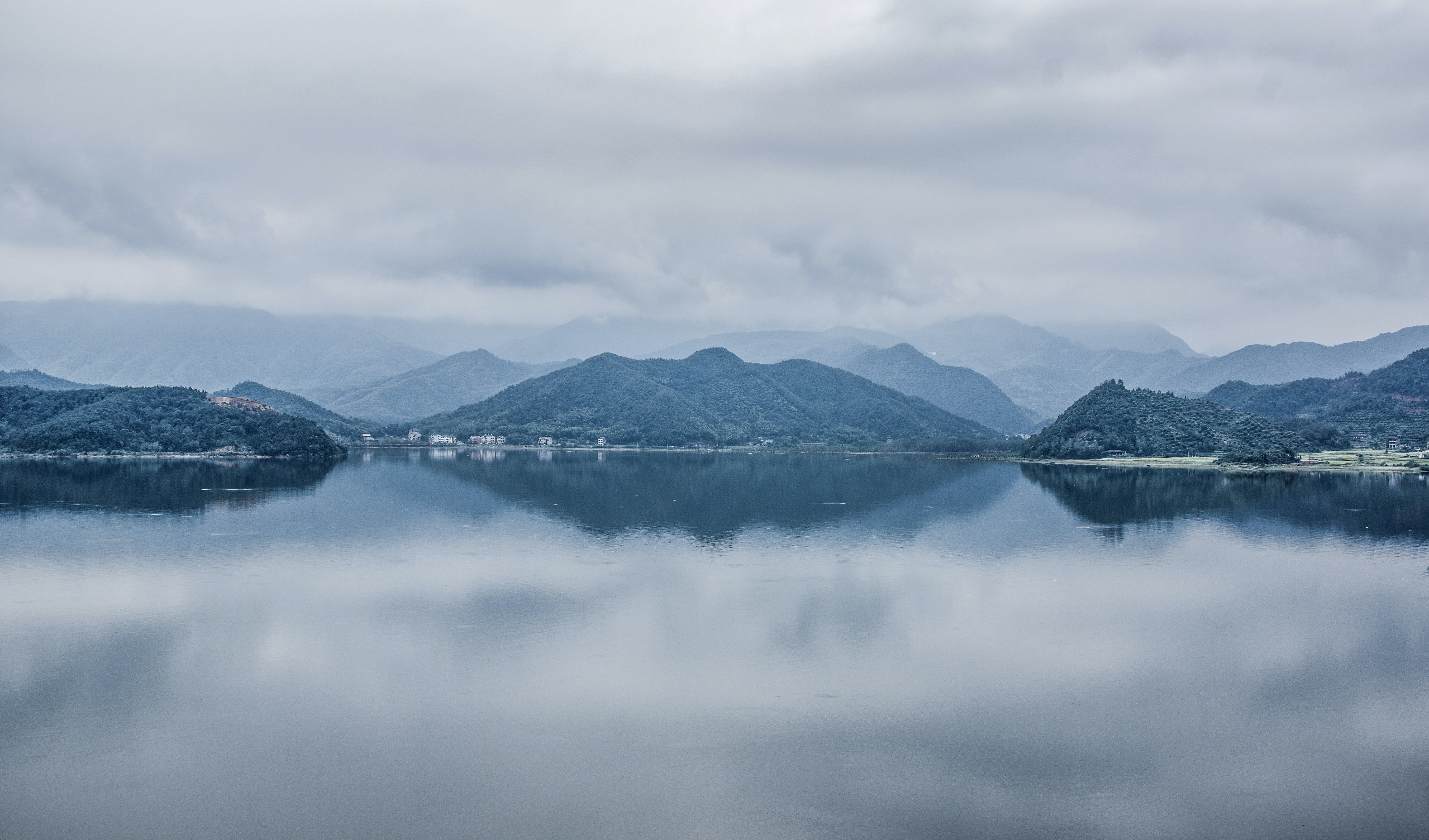 View from a calm lake on its hilly shores