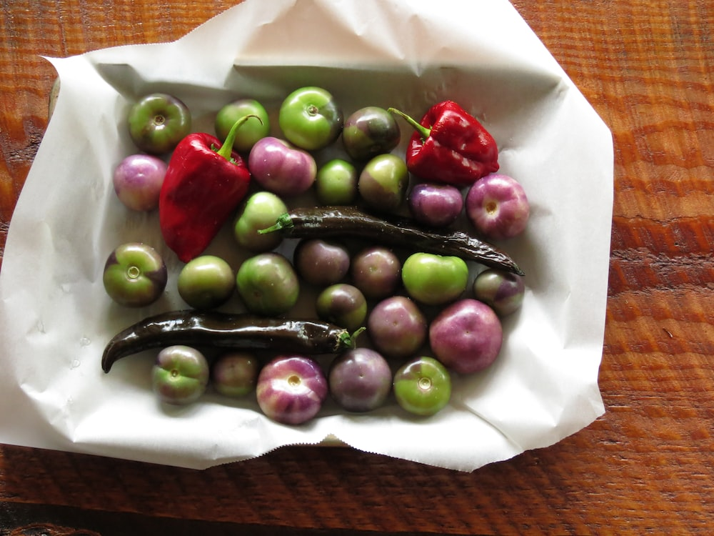 green and purple tomatoes and red bell peppers in white paper