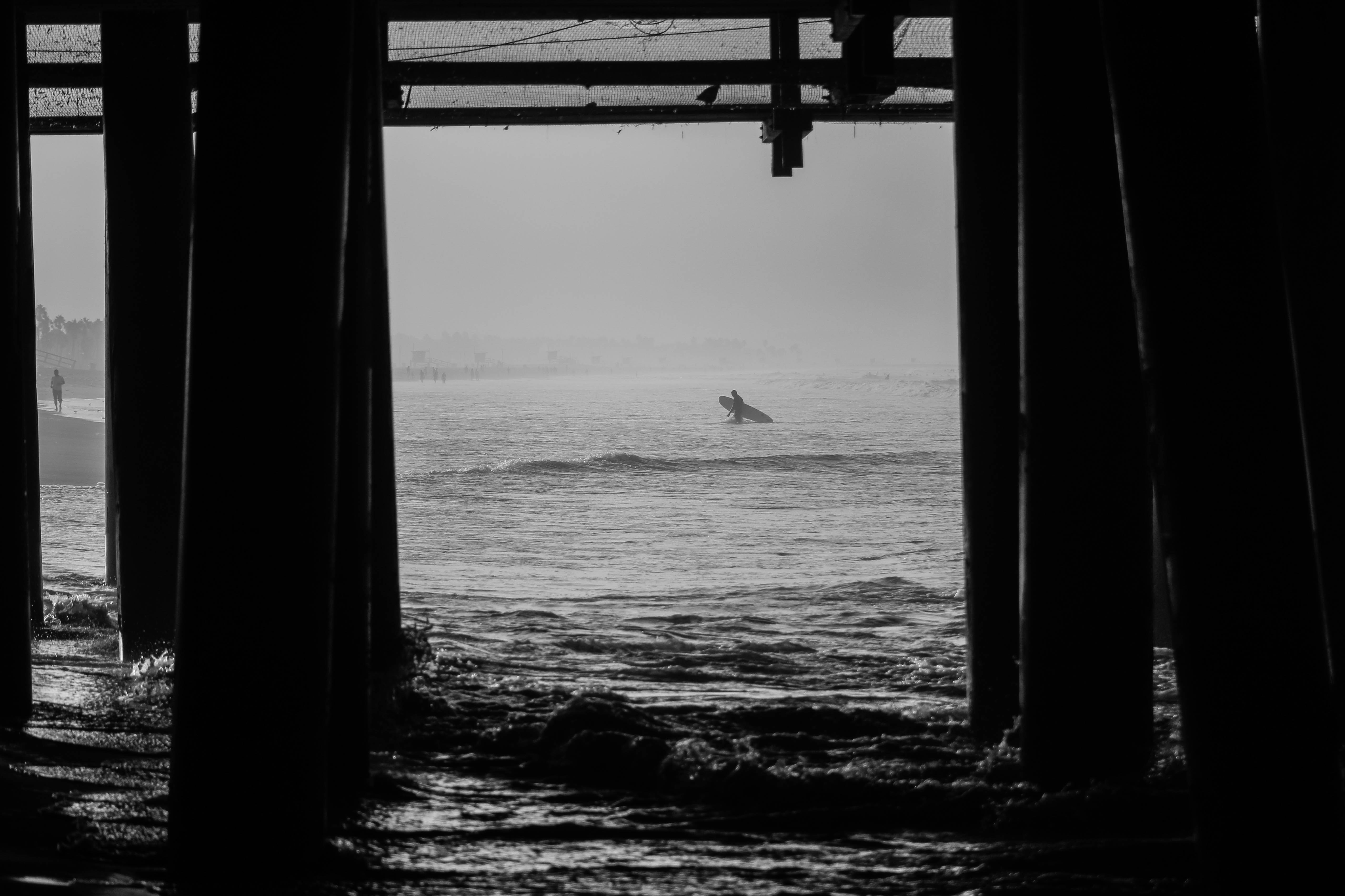 Surfer with a surfboard viewed through pier pillars at Santa Monica State Beach in black and white