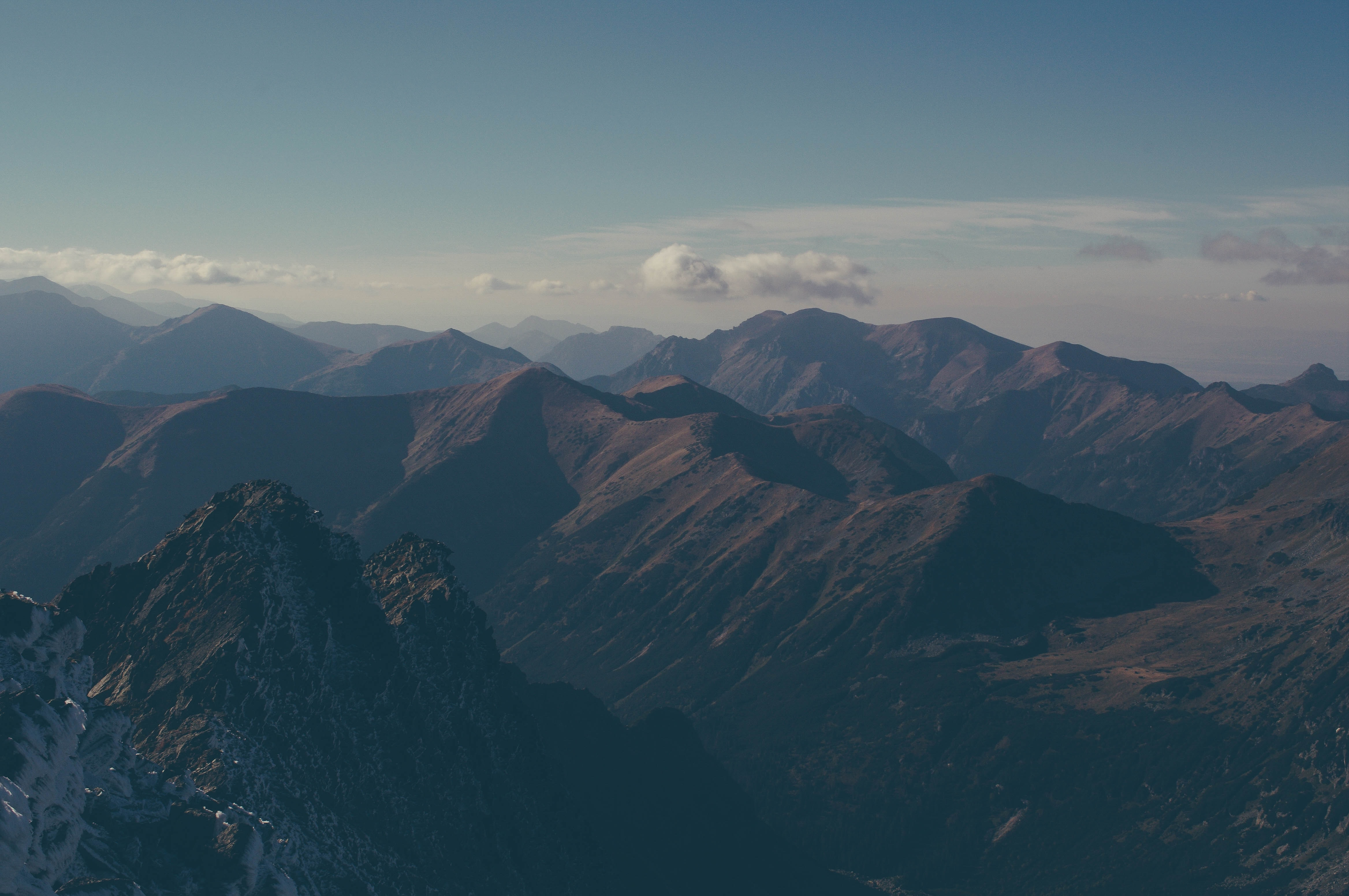 Tall peaks and sharp ridges stretch to the horizon under a pale blue sky
