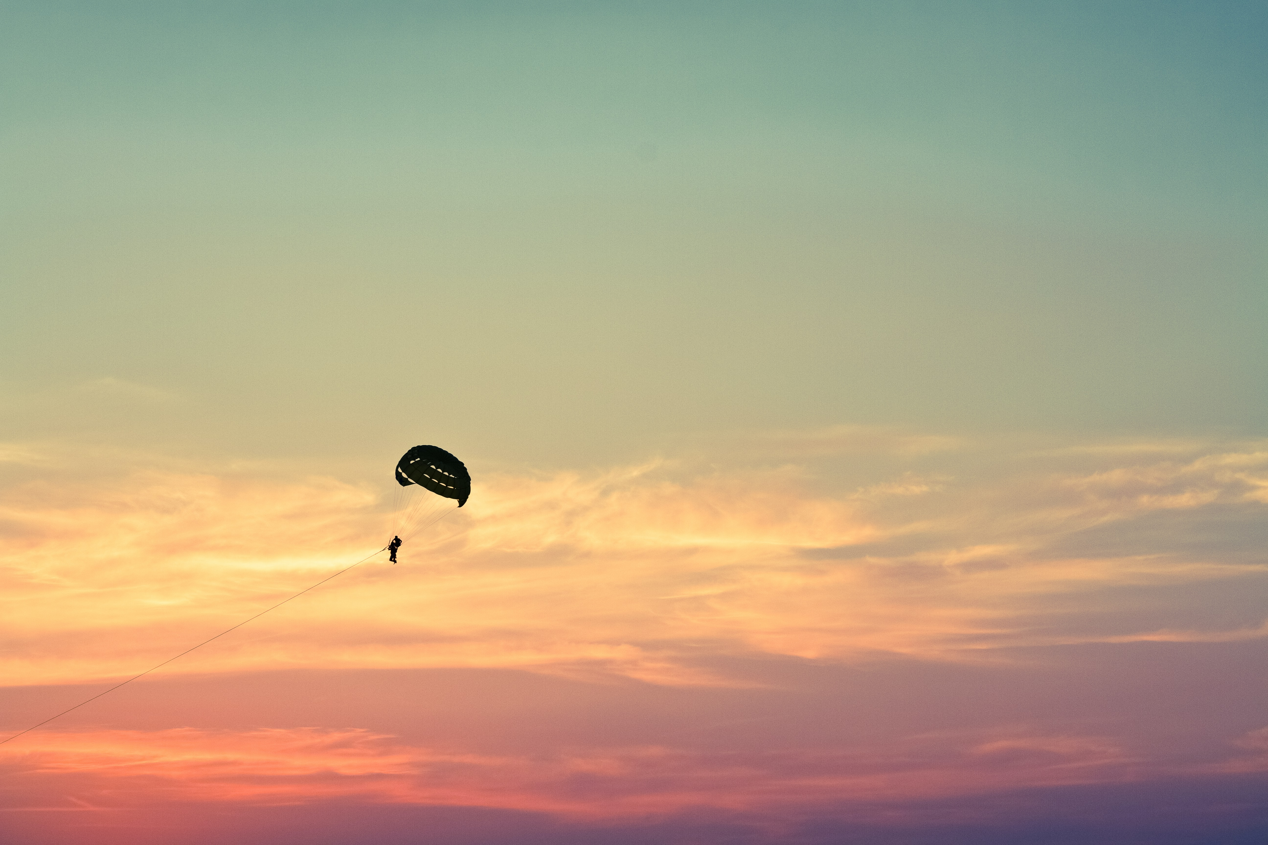 A silhouette of a paraglider in the sky during the golden hour