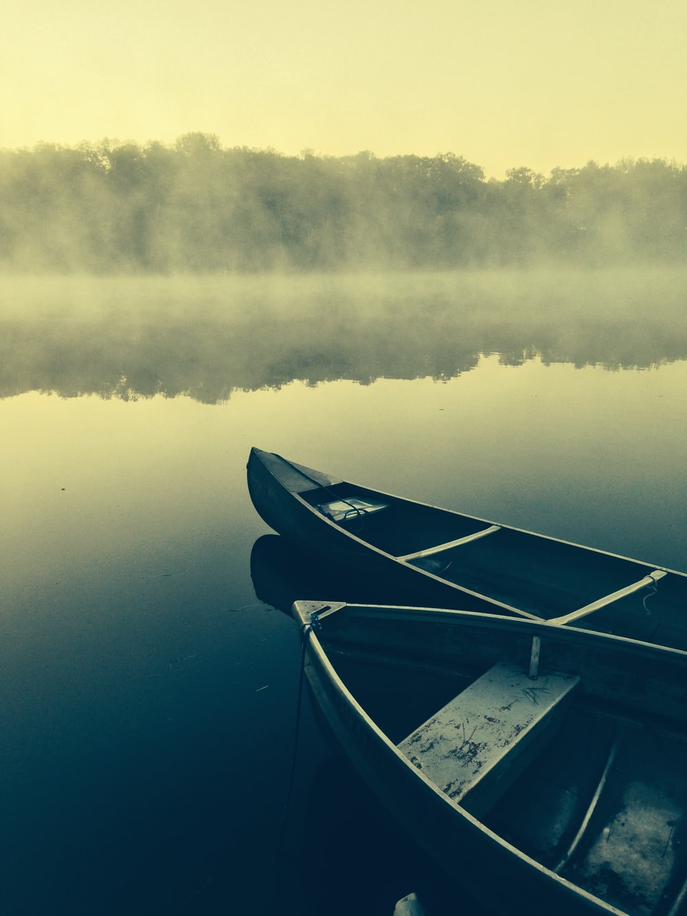 two gray canoes on misty body of water