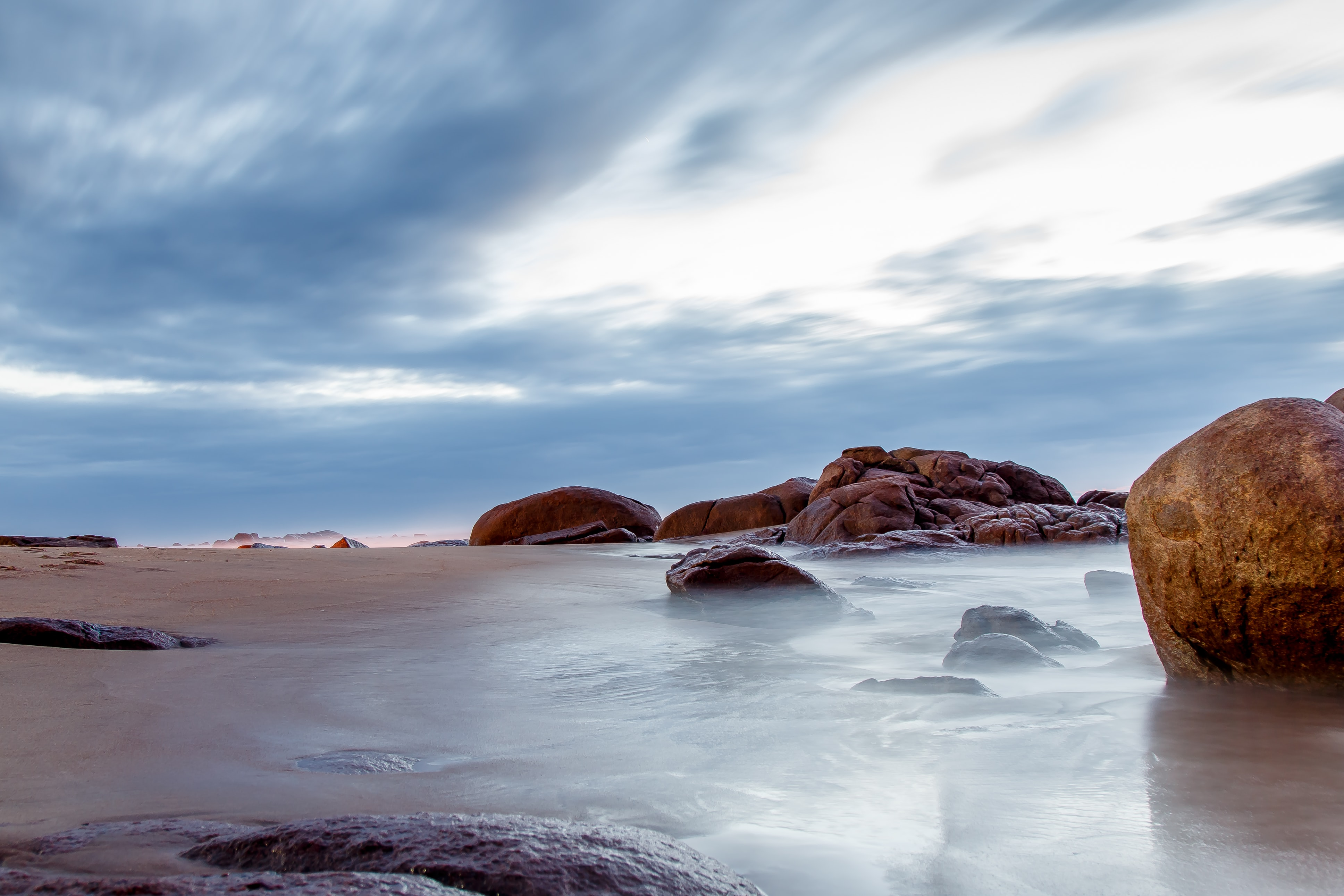 Smooth round rocks in wet sand and shallow sea water
