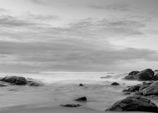 grayscale photo of rock formation surrounded with body of water