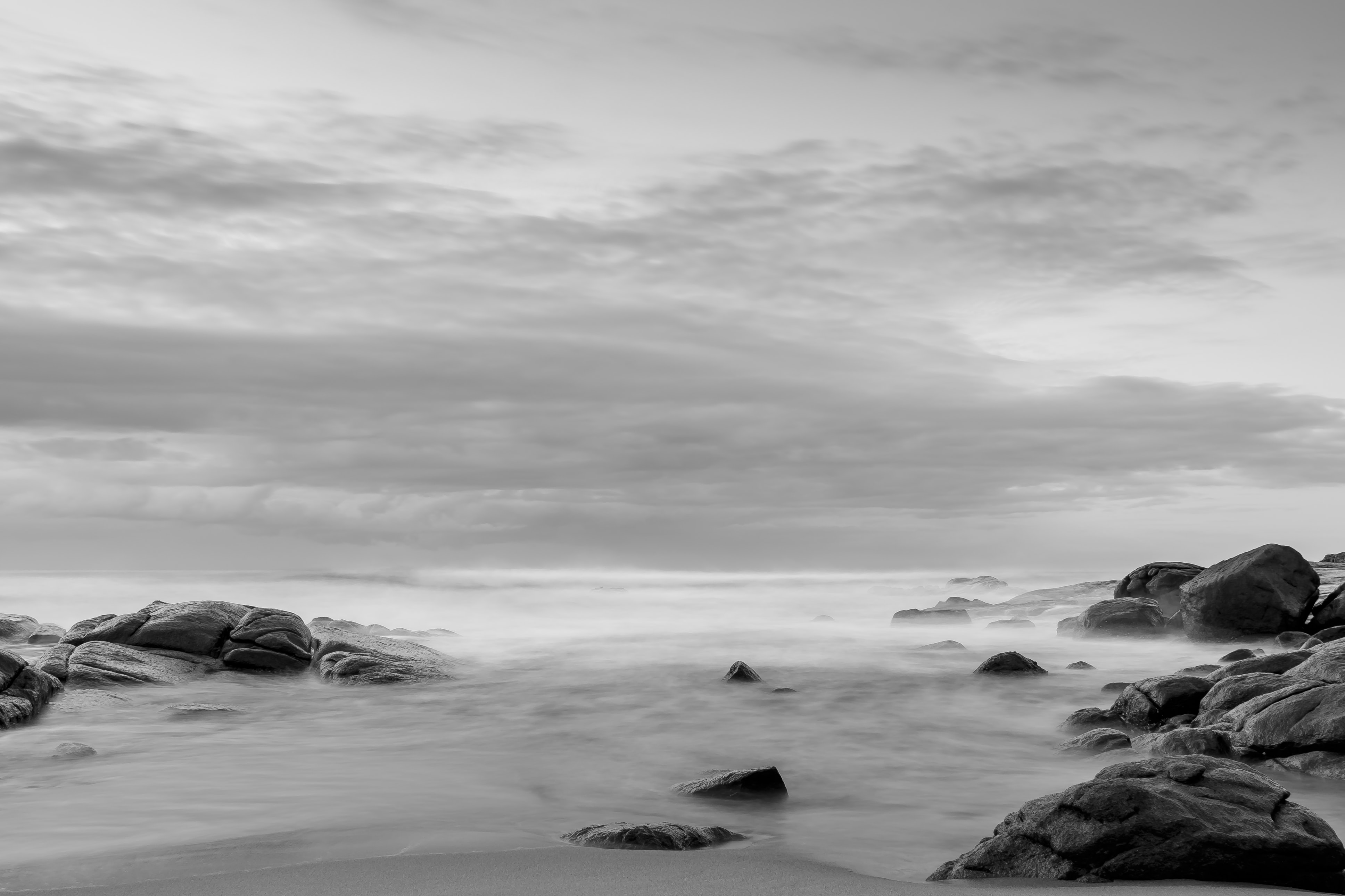A black-and-white shot of the hazy seashore with smooth rounded rocks jutting out from the sand