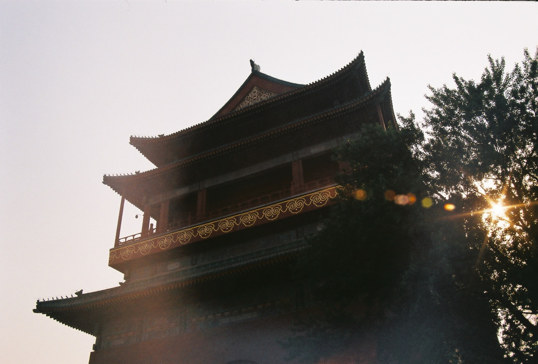 Tall traditional Asian house with a sun shining through a tree