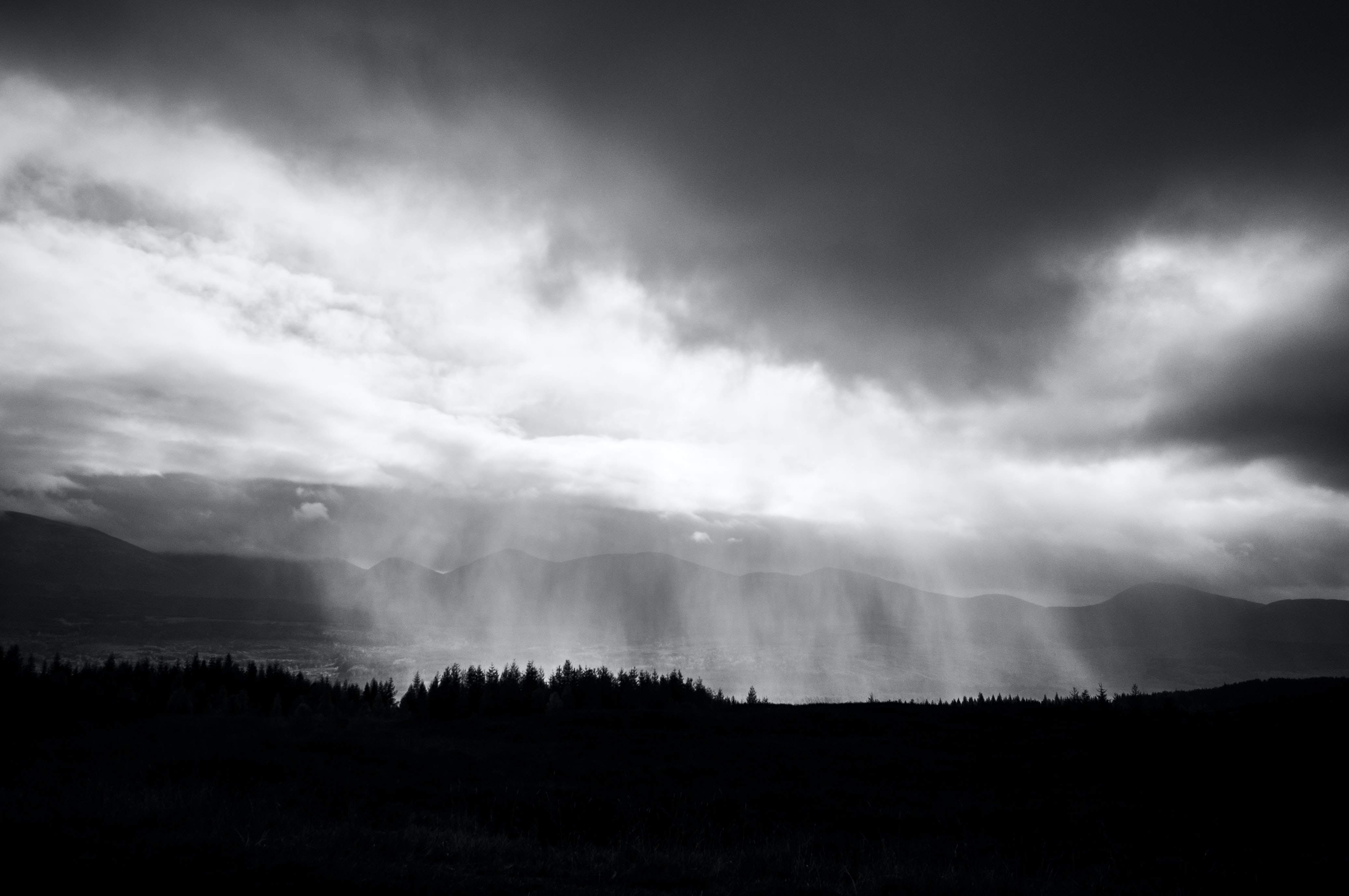 A black and white photo of heavy rain clouds over a lake