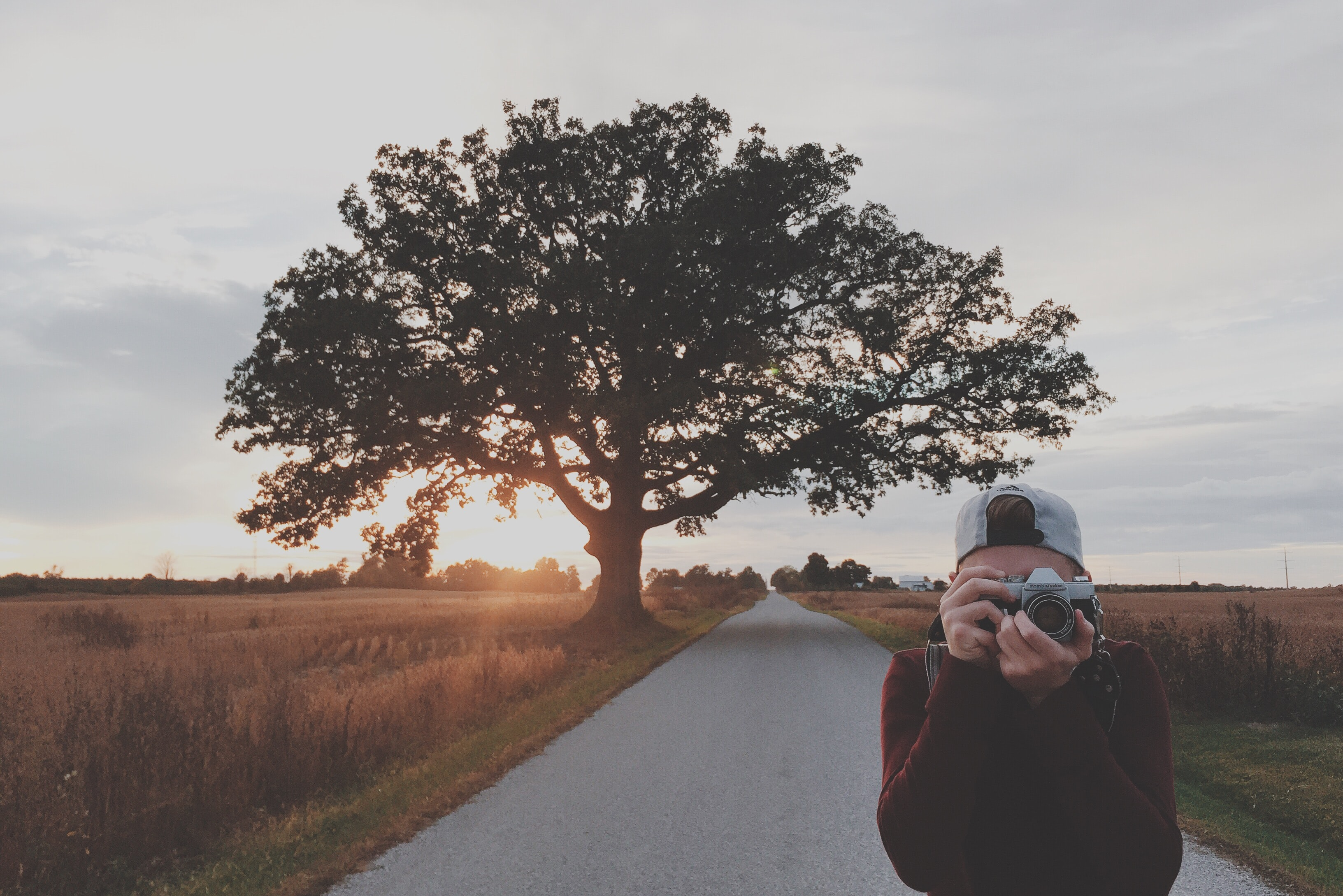 A young man with a camera taking pictures on an empty rural road