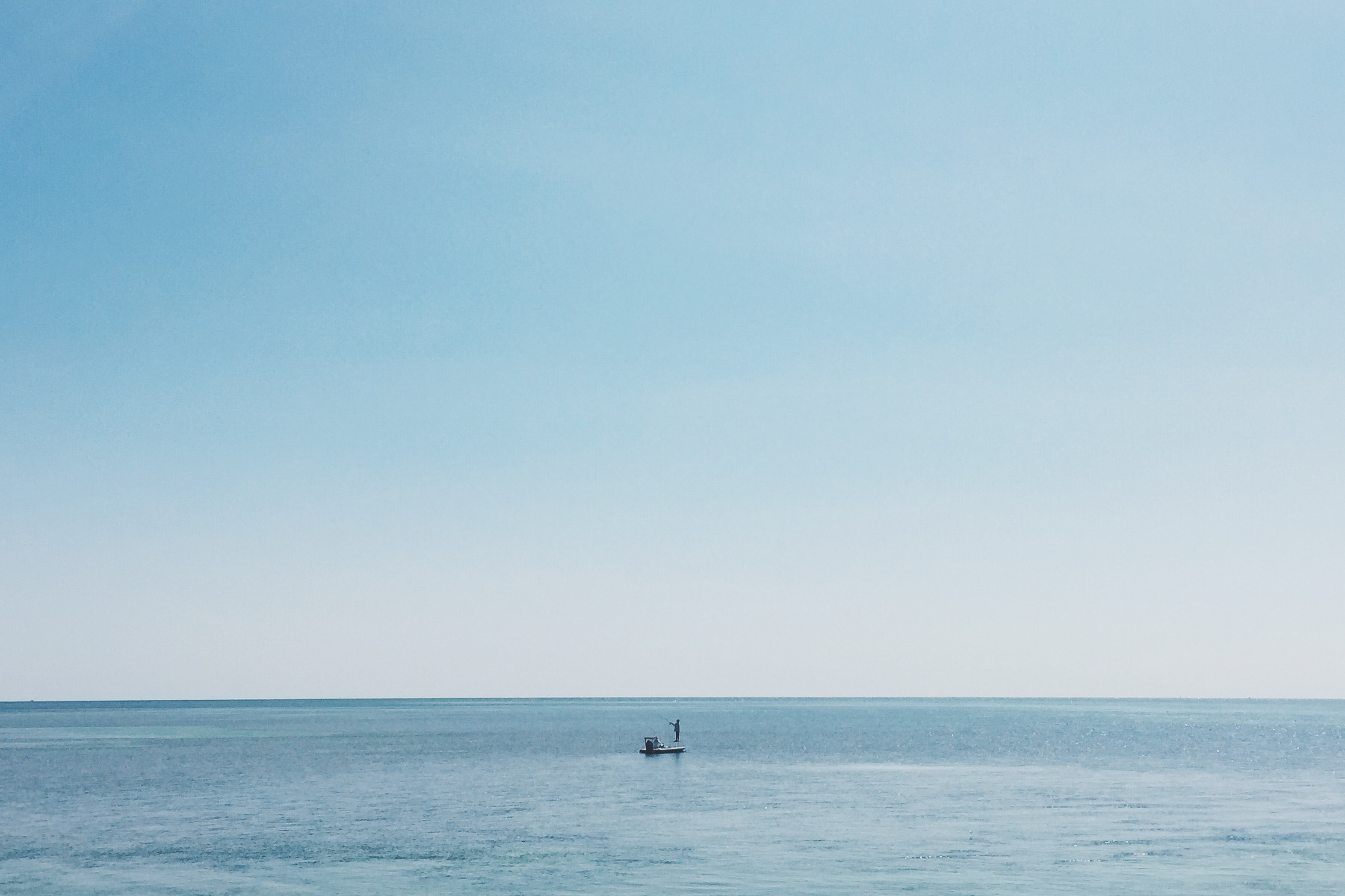 A fisherman on his boat on the calm ocean where the water meets the horizon