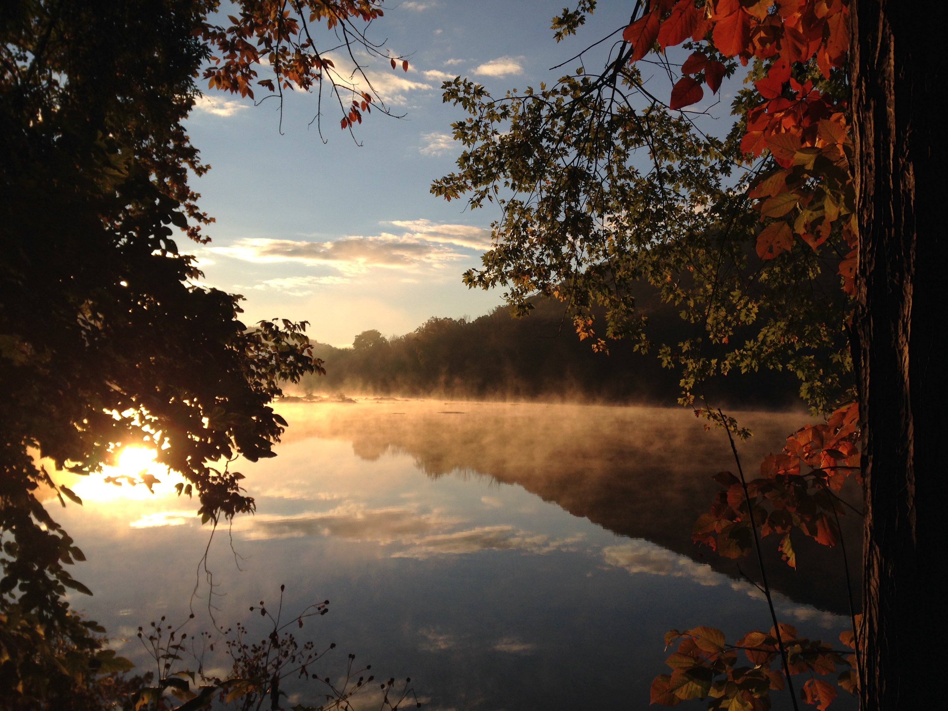 The sky reflecting on a misty lake with orange rays from the sunset in autumn