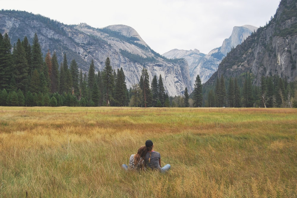 two person sitting on grass field