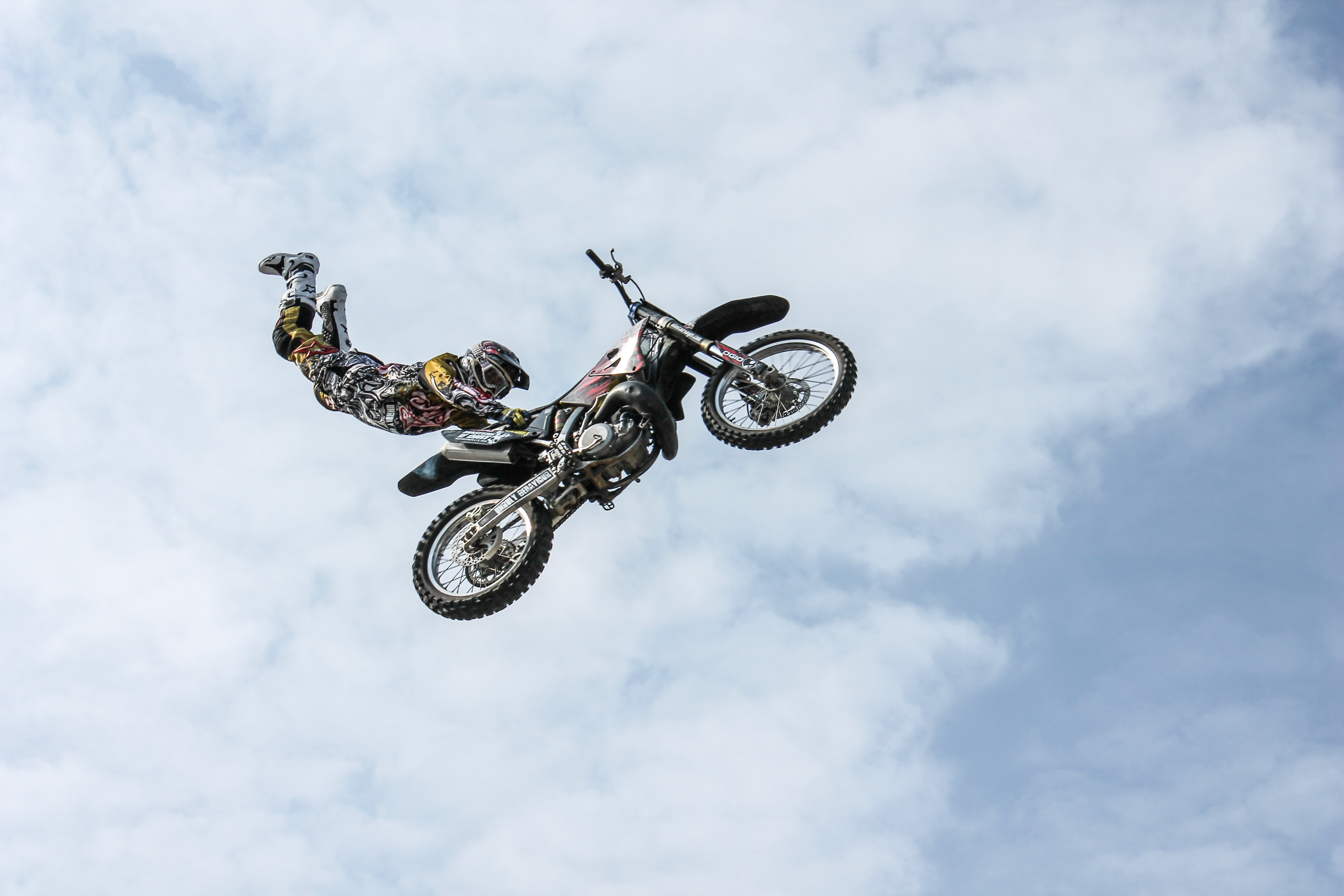 A motocross biker doing a handstand in the air on his motorcycle